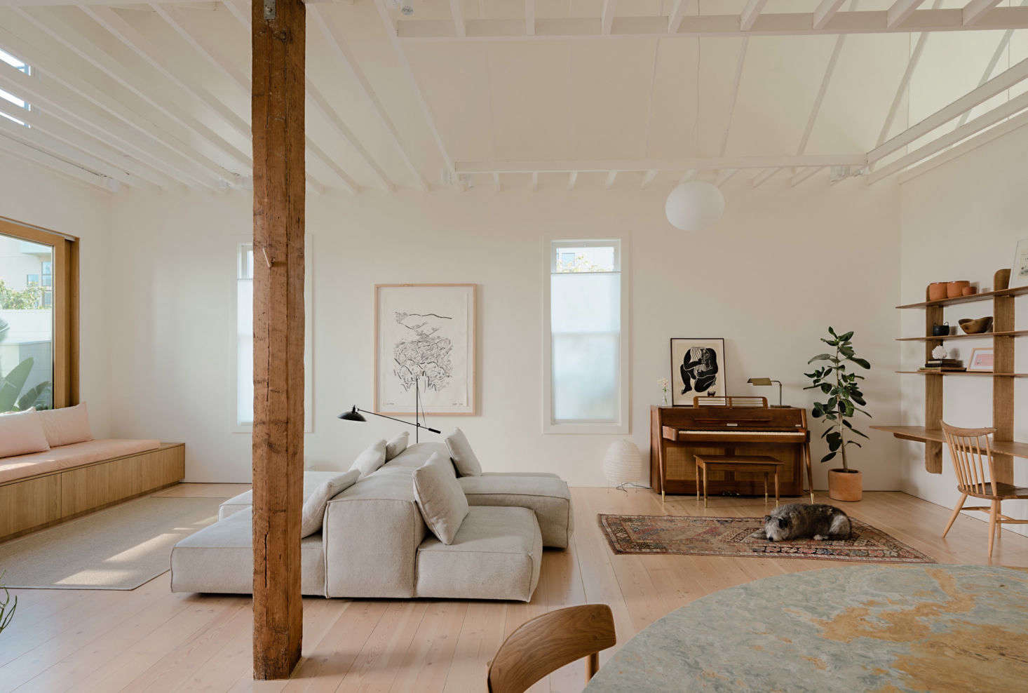 """""""I'm regularly inspired by Japanese and Scandinavian design, and the tradition of respecting natural materials, the craft of building, and the beauty of a well-considered space,"""" Ryan says of his design sensibility. The older building was reimagined for easy entertaining, something the clients do often. The original rafters in the open living room were painted over and the timber columns refinished. The Extrasoft Sofa is a Piero Lissoni design."""