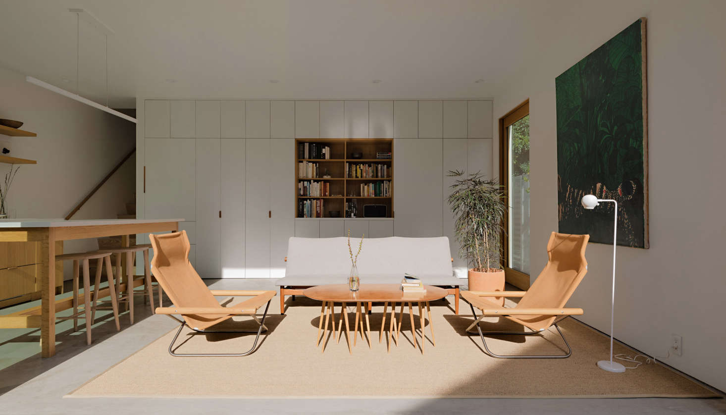 """Concealed in the wall of cabinets is a powder room. The """"Japan Sofa"""" by Finn Juhl, a multi-legged coffee table, and a pair of armchairs by Takeshi Nii—all vintage—make up the living area."""