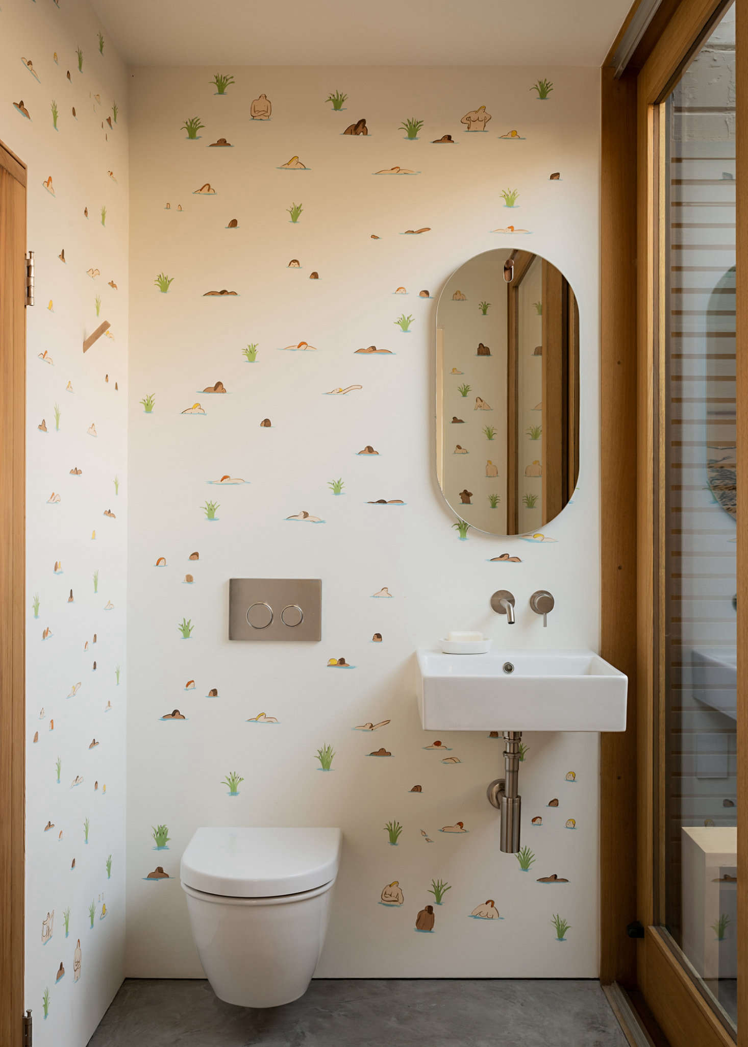 An onsen-inspired bathroom features a hand-painted mural of bathers by local painter Rob Moss Wilson. Sliding doors open into an outdoor bathtub and shower.
