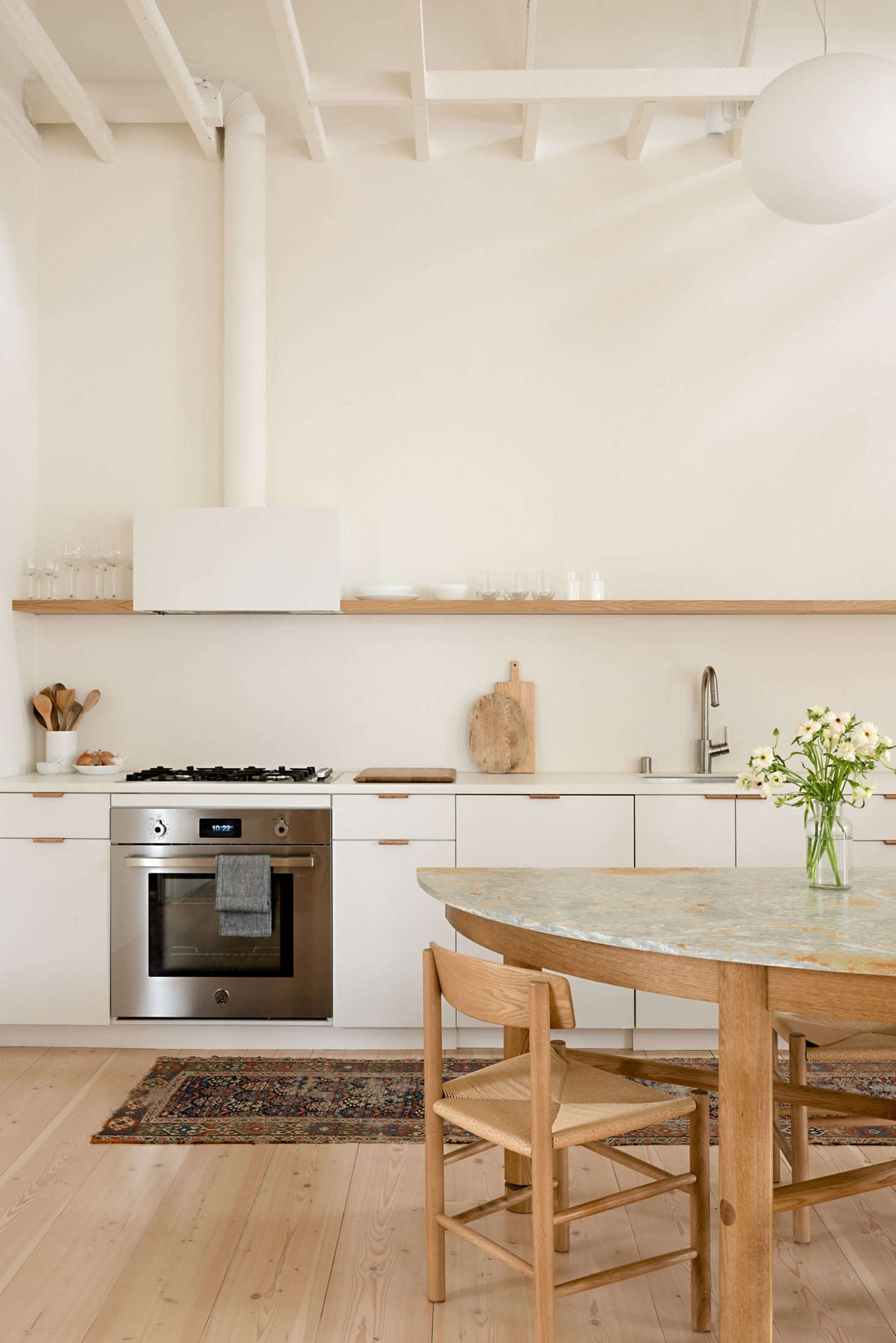 The adjacent kitchen. The white oak dining table and wall storage system were built by the owners' good friend, Anthony Zollo of Studio Zollo. The dining chairs are by Borge Mogensen.