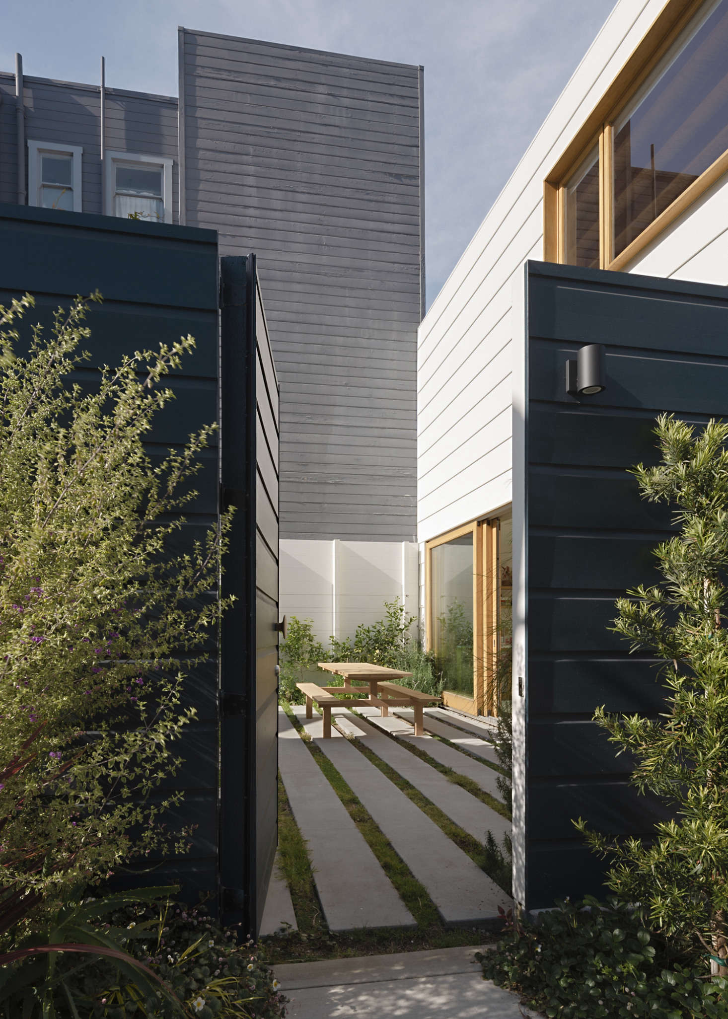 """The street entrance opens into the private courtyard. """"The custom-profile painted siding echoes the typical horizontal lap siding seen throughout the neighborhood while playing with scale,"""" says Ryan."""
