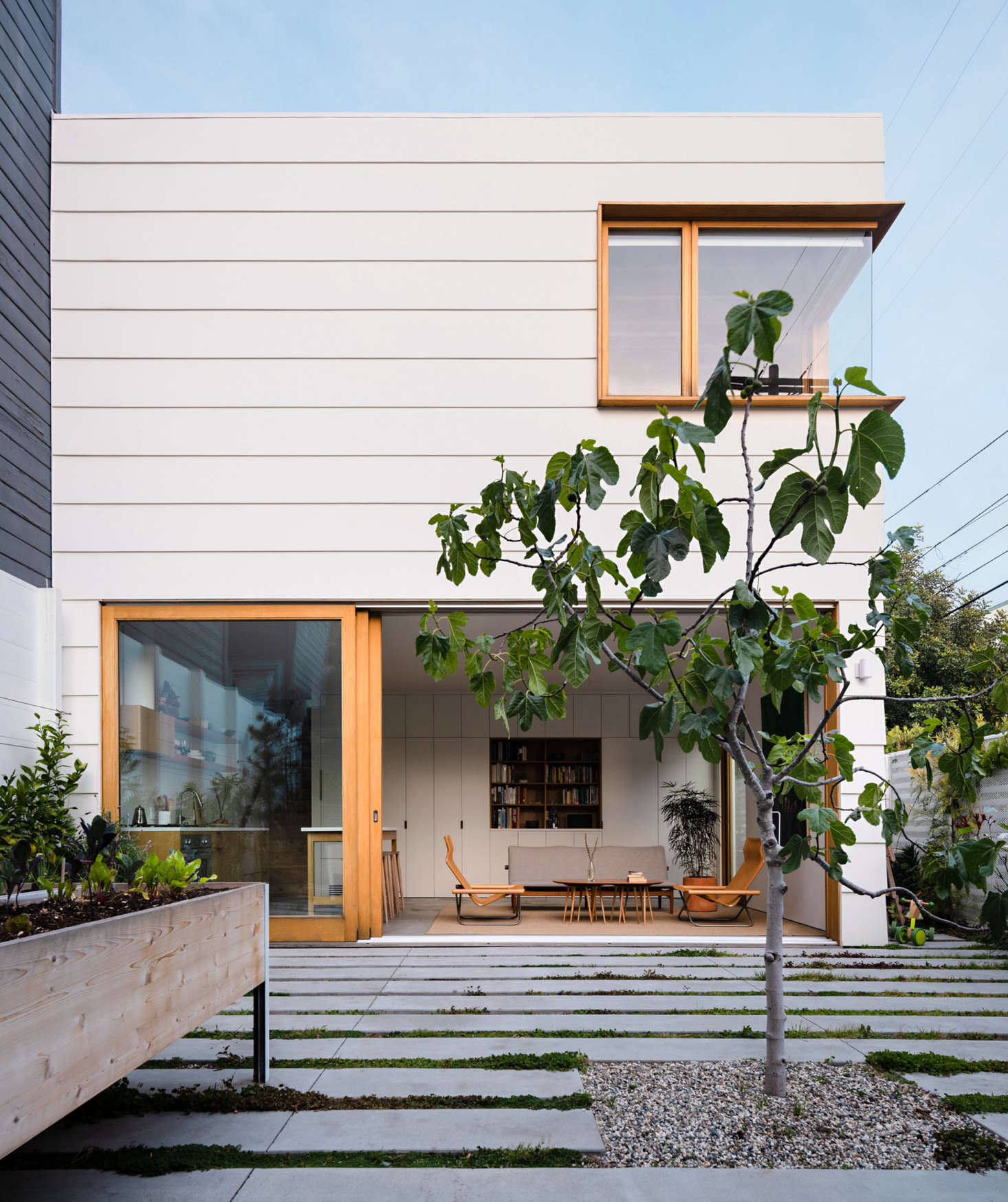 The new two-story structure, designed with its own open living room and kitchen. The exposed concrete flooring continues into the garden with a series of linear pavers, interspersed with rows of sedum. A fig tree grows in the center of the courtyard.