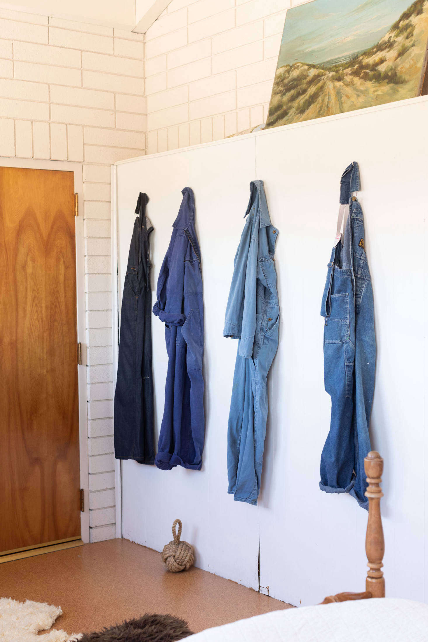 A row of work overalls and jumpsuits create a beautiful vignette.