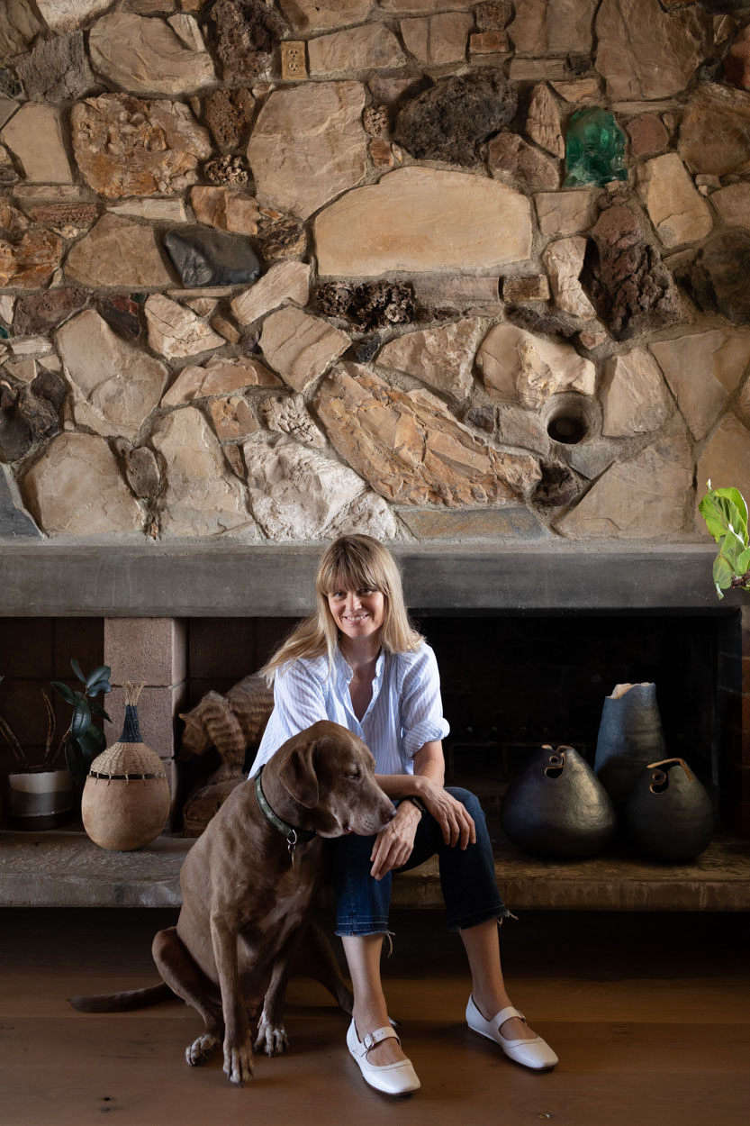 Brownie and Wilkinson in front of the fireplace, integrated into a stunning stone wall.