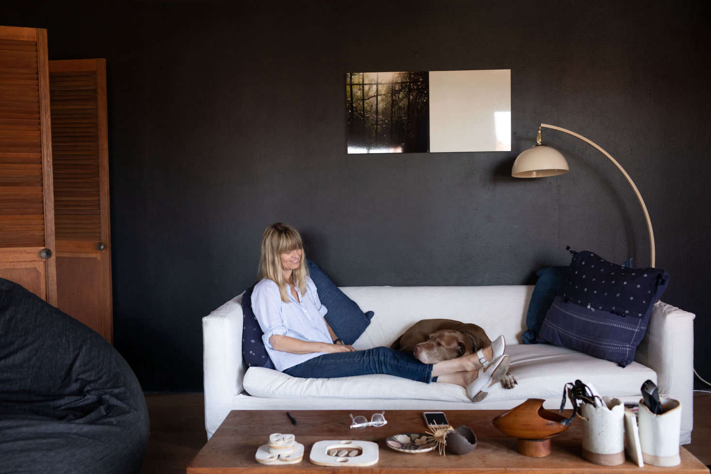 Wilkinson, a British transplant, with her loyal sidekick, Brownie. Displayed on her coffee table are some of her ceramic works. Her home is situated high up in the hills and rests under the glare of direct sunlight; dark interiors offer a cool respite.