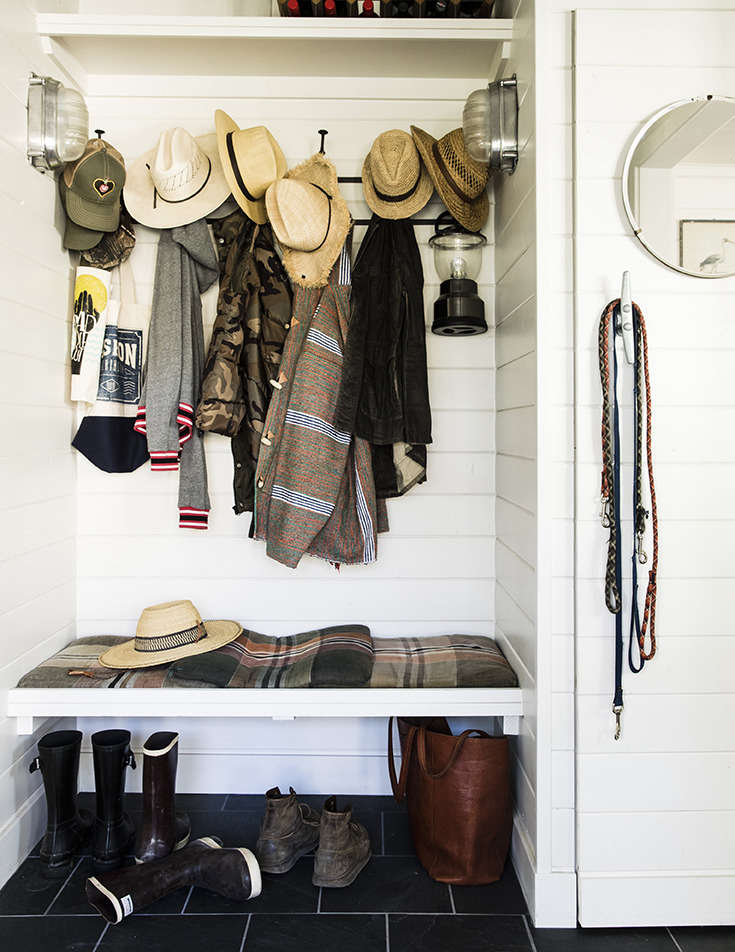 The hardworking mudroom, complete with sturdy hooks; a round porthole-like mirror; a nautical cleat door handle (and improvised leash holder); and industrial nautical sconces. (See Nautical Hardware: 7 Cleats for Home Use.)