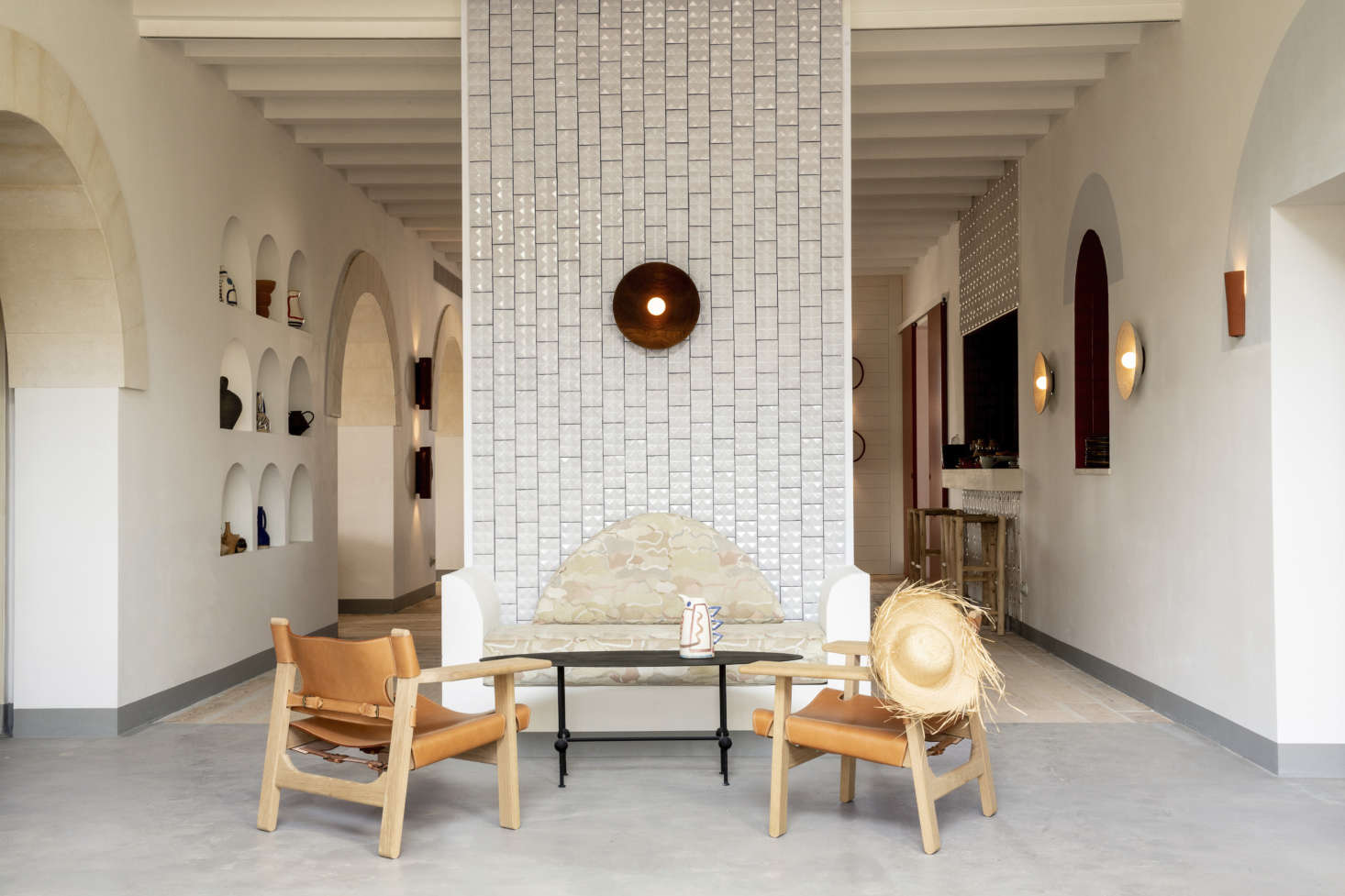 In the lobby, Portuguese tiles line a dividing wall with a seating ensemble that includes Borge Mogensen Spanish Chairs and a concrete banquette that echoes the lines of the surrounding archways. Meilichzon put teams of local craftsmen to work on the custom furnishings.