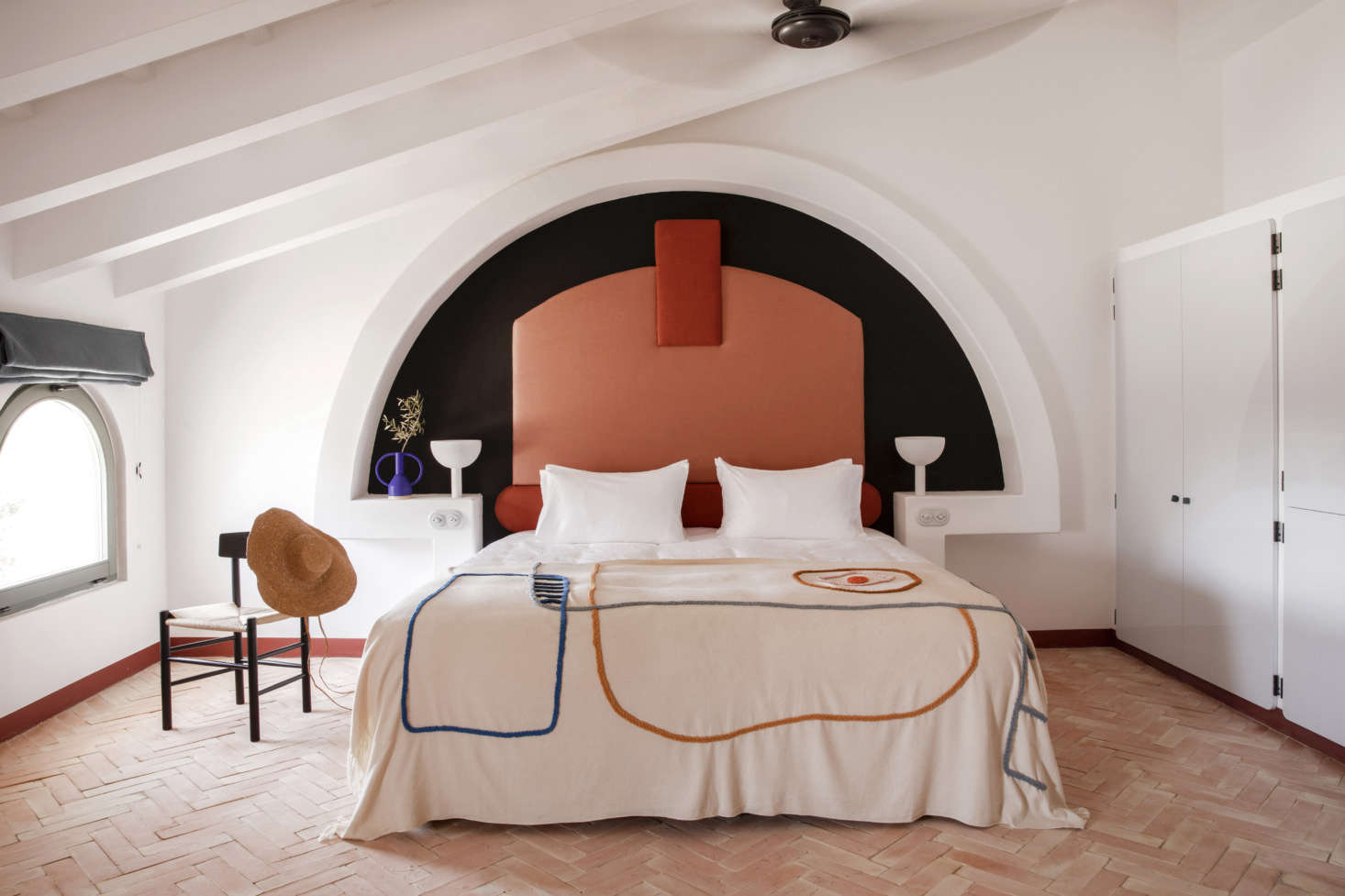 Meilichzon is known for her inventive beds—and never repeats herself. At Menorca Experimental, she built altar-like concrete alcoves finished in white lime and inset with upholstered headrests in two shades of terra-cotta. The embroidered cotton bedspreads were made for the hotel by textile and ceramic studio LRNCE of Morocco. The herringbone floor is composed of terra-cotta.