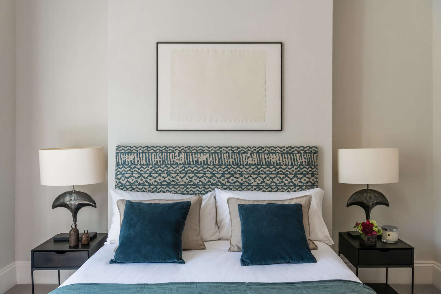 """Olivia and her boyfriend's bedroom. Olivia stapled Khari blue linen fabric by Mark Alexander to an old headboard that once belonged to her mother. """"I spent two months with different fabrics draped over the bed, testing out the styles,"""" she shares. The Porta Romana lamps were scored at a sample sale; the bedside tables from La Redoute were purchased at a steep discount. The walls here are painted French Grey by Little Greene."""