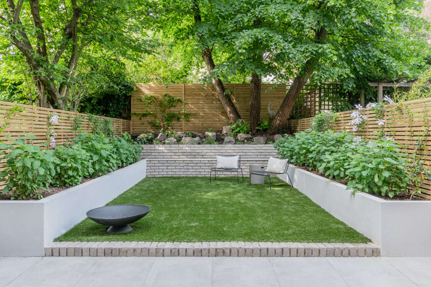 """Large ceramic tiles from Solus Ceramics make up the patio. (""""These are far cheaper than concrete and won't chip as easily,"""" notes Olivia.) The privacy fencing is fabricated from Iroko wood. As for the grass, it's artificial. """"It is the best thing for maintenance when you all have busy careers,"""" she explains."""