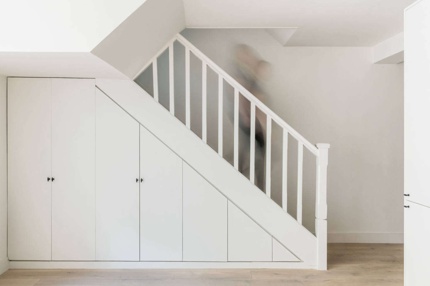 """The cast iron pulls show up here on closets integrated into the staircase. The flooring is engineered oak by Havwoods. """"We invested in engineered timber floors on the ground floor, where people are going to be entertaining, and saved money by laying carpet down upstairs. The carpet also means my sister doesn't hear footsteps above,"""" explains Olivia."""