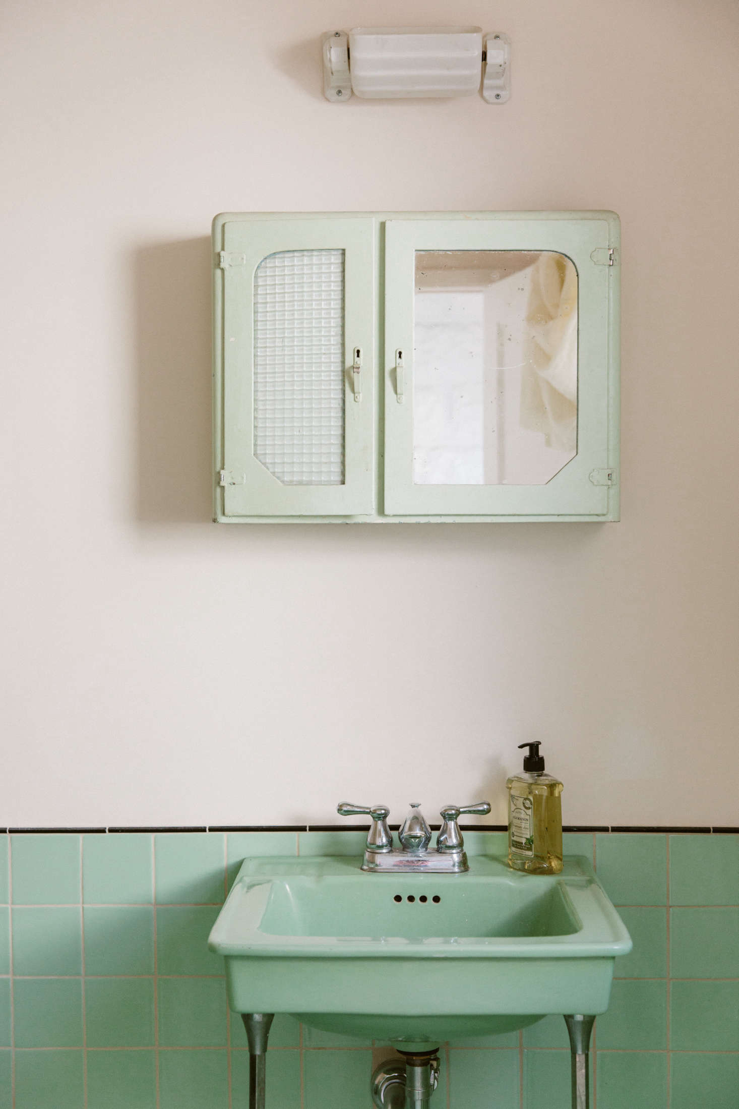 """The shop's bathroom only looks like it's been there forever. """"There was an existing bathroom, but it had seen better days,"""" O'Rourke says. """"We replaced all the fixtures with the antique minty-colored ones, also sourced locally in LA; then we found new tiles to match."""""""