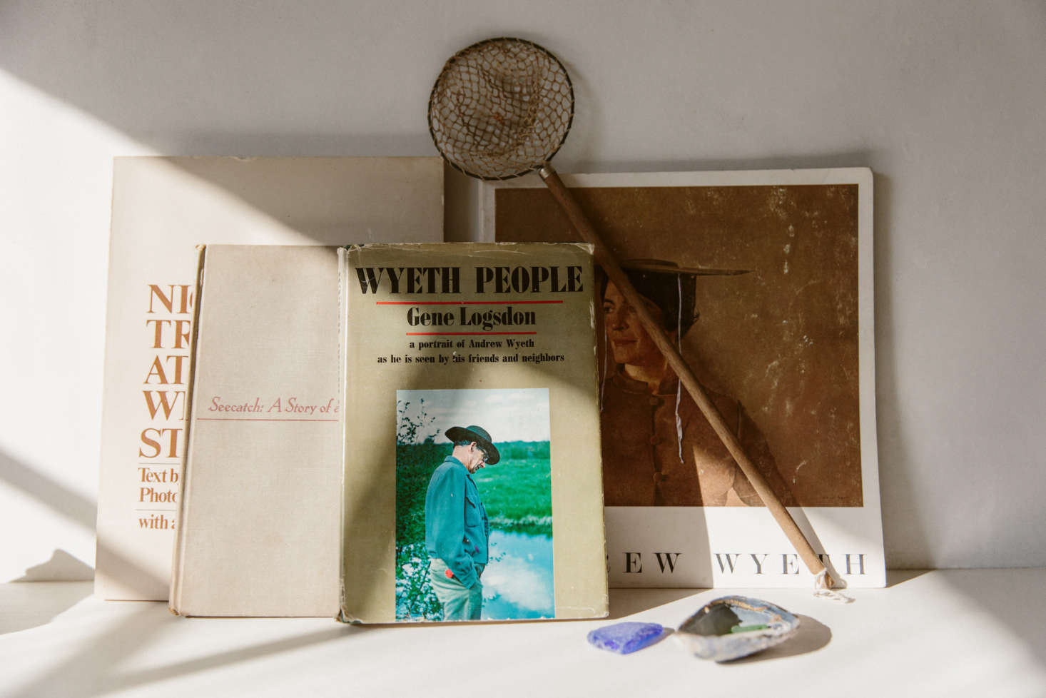 """O'Rourke kept the bones of the space simple, and leaves the evocativeness to the tiniest details she places throughout the shop: vintage books on Wyeth, shown here; or, elsewhere, a miniature mirror (not pictured) and a children's chair. """"The small mirror I bought off of Etsy from a little shop in France,"""" she says. """"I actually had no idea how tiny it was until it arrived, but it is just absolutely perfect in every way, even the little angle that it sits at."""""""