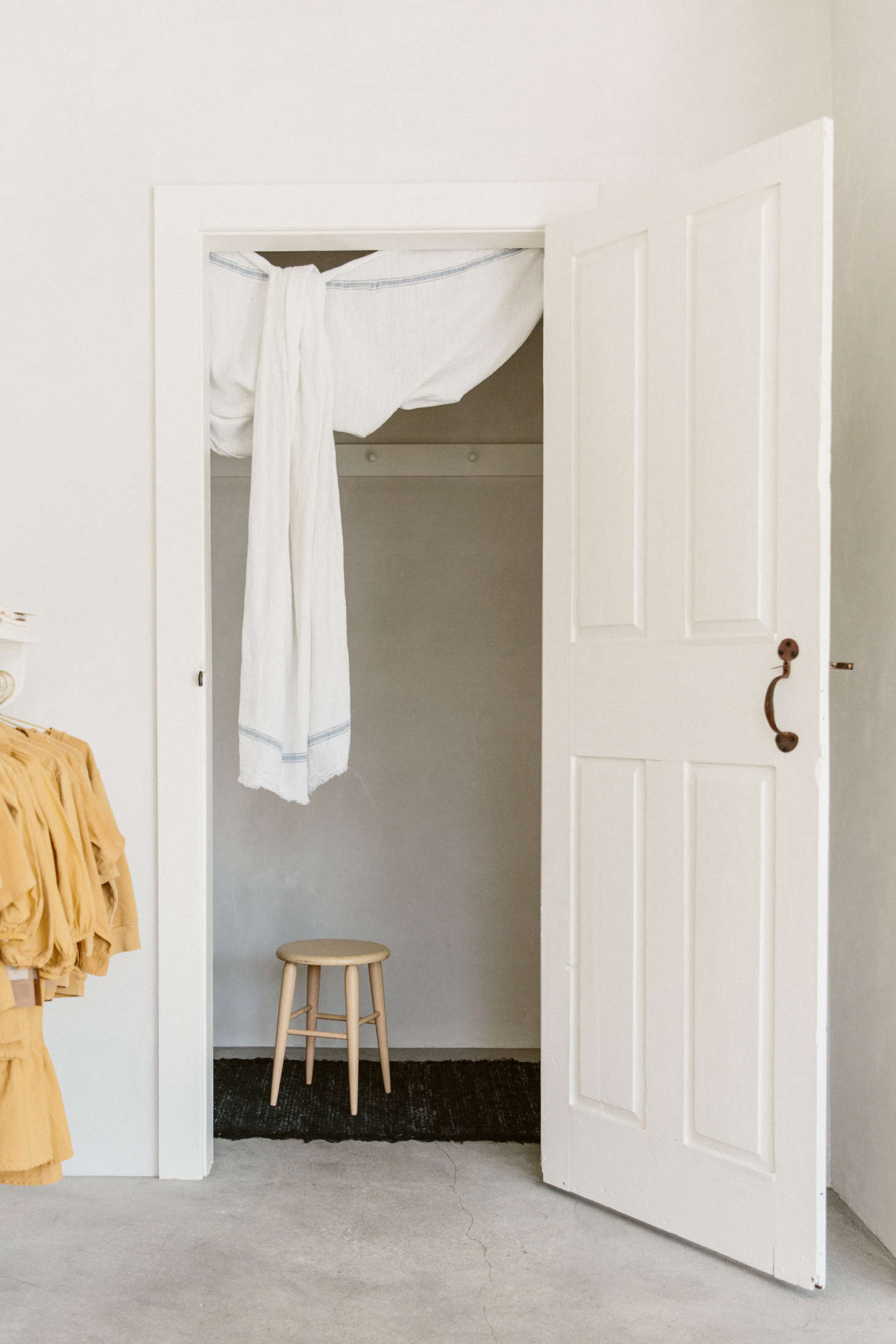 The doorway to the shop's petite dressing room is draped with a simple cloth, as is the back doorway (scroll down for a photo)—an effortless solution for leaving doors open and letting in the breeze.