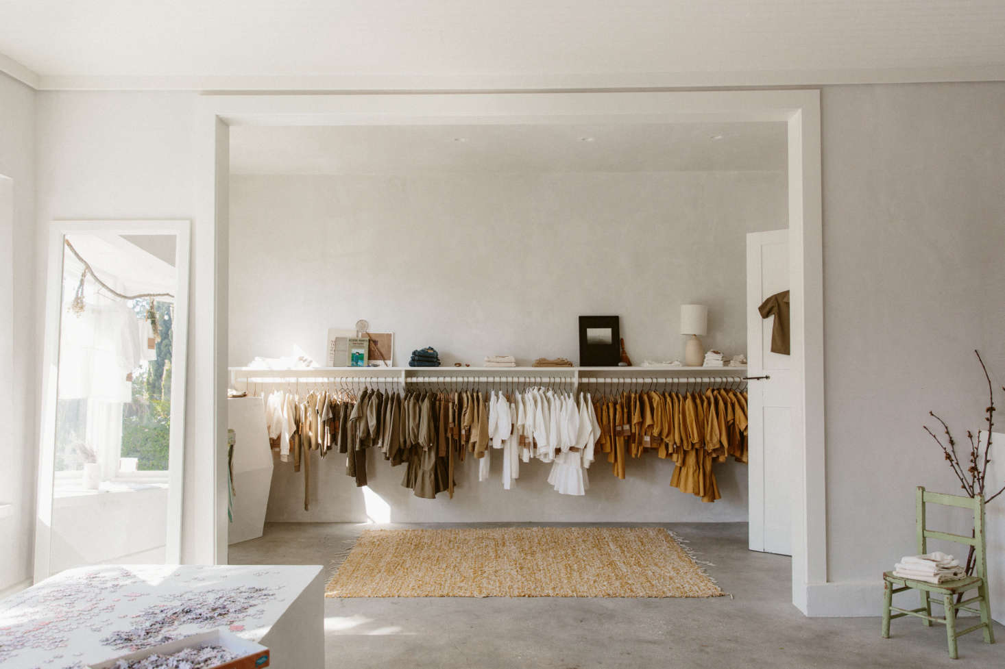 O'Rourke uses doorways and windows as opportunities for framing rooms and vignettes. Here, a wide, ceiling-high opening—set off by a floor mirror, at left; a small chair, at right; and a natural-fiber rug beyond—creates a thoughtful composition. The focus is always O'Rourke's plant-dyed clothing for children and adults, dyed with natural materials and sewn in LA.