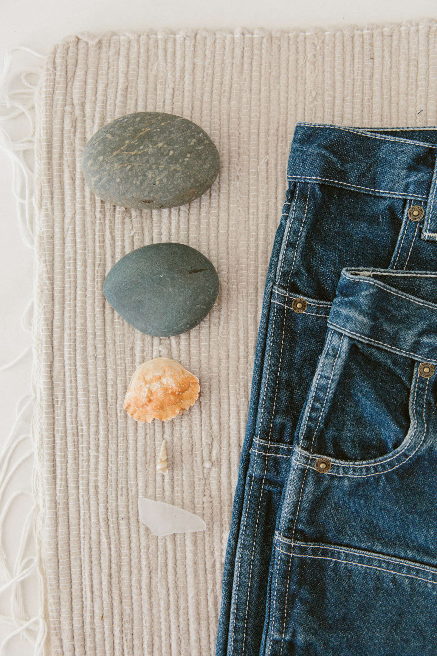 Smooth rocks and a hollow crab shell next to some Rudy Jude denim.