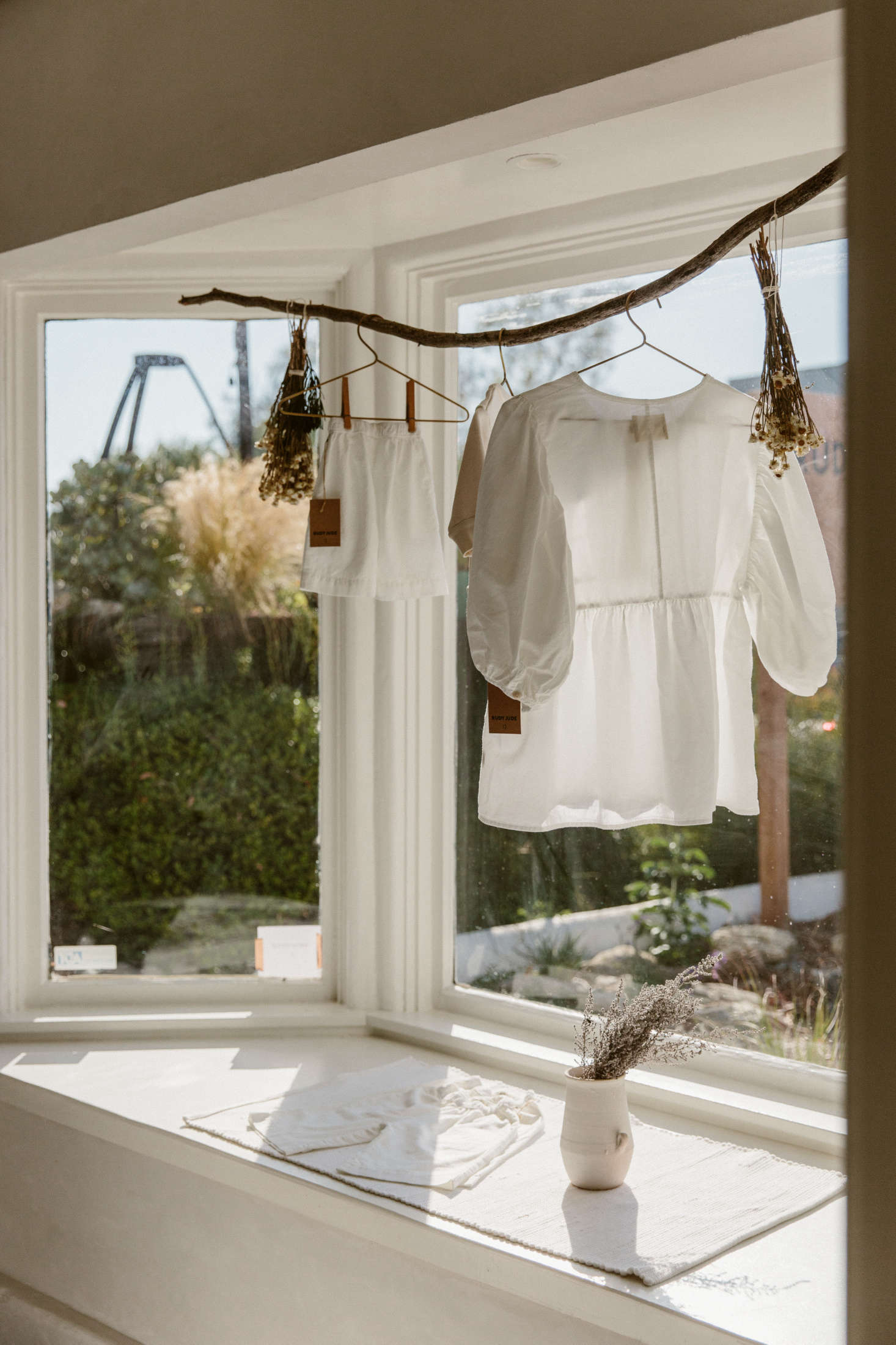 In the front window, a curved branch displays a Rudy Jude Day Blouse—and bundles of dried flowers. (For more ideas like this, seeThe New Rusticity: 11 DIY Ways to Use Branches Indoors.)