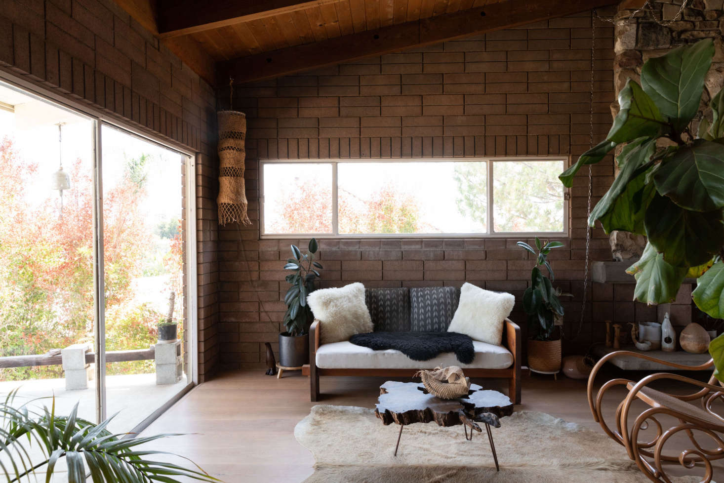 Wood-paneled ceilings and brick walls keep the house cool on hot days. Hanging in the corner is one of her woven raffia creations.