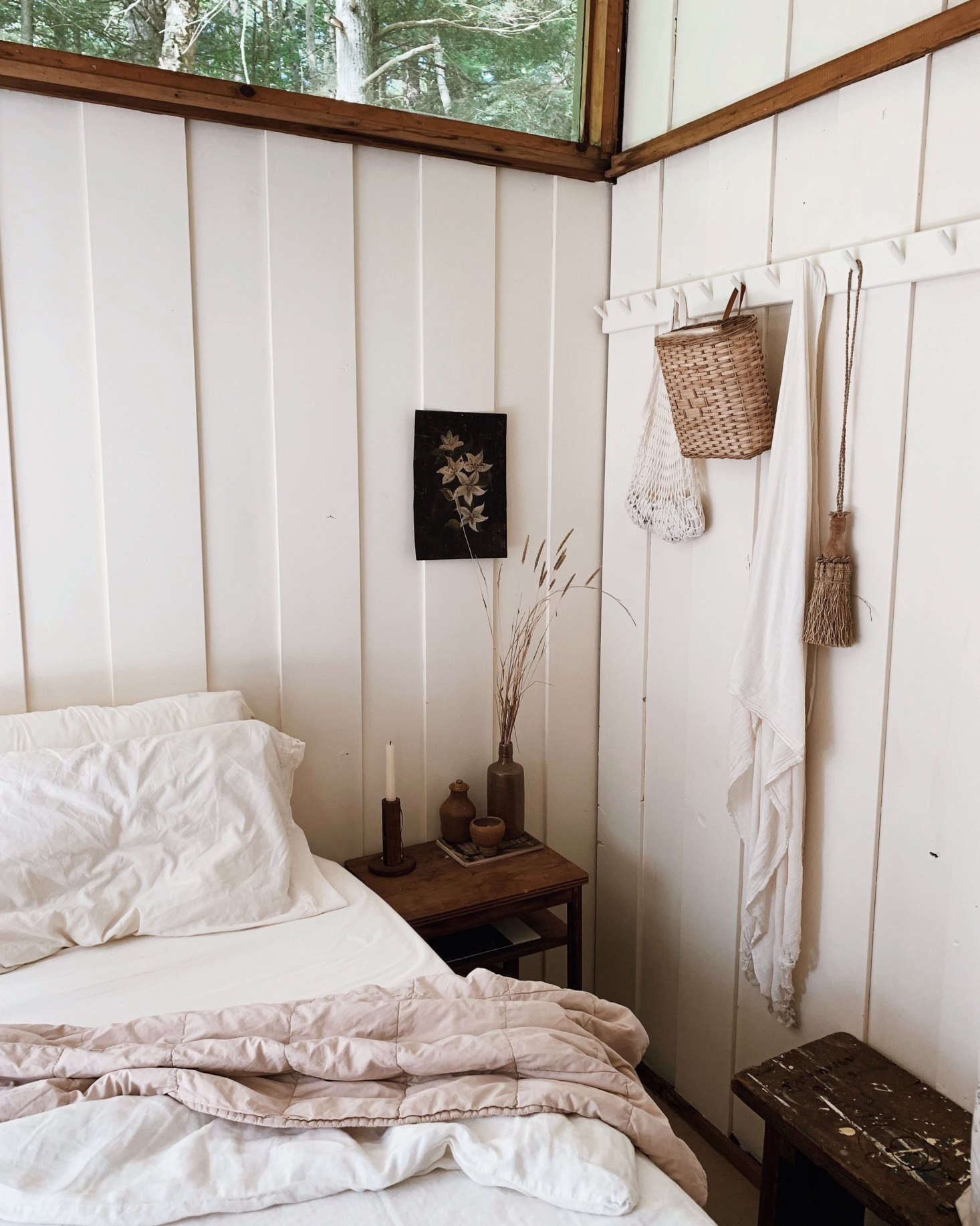 The bedroom is set for an off-the-grid weekend away, with bedside candlesticks collected from a nearby antique shop and a peg rail from The Foundry Home Goods.