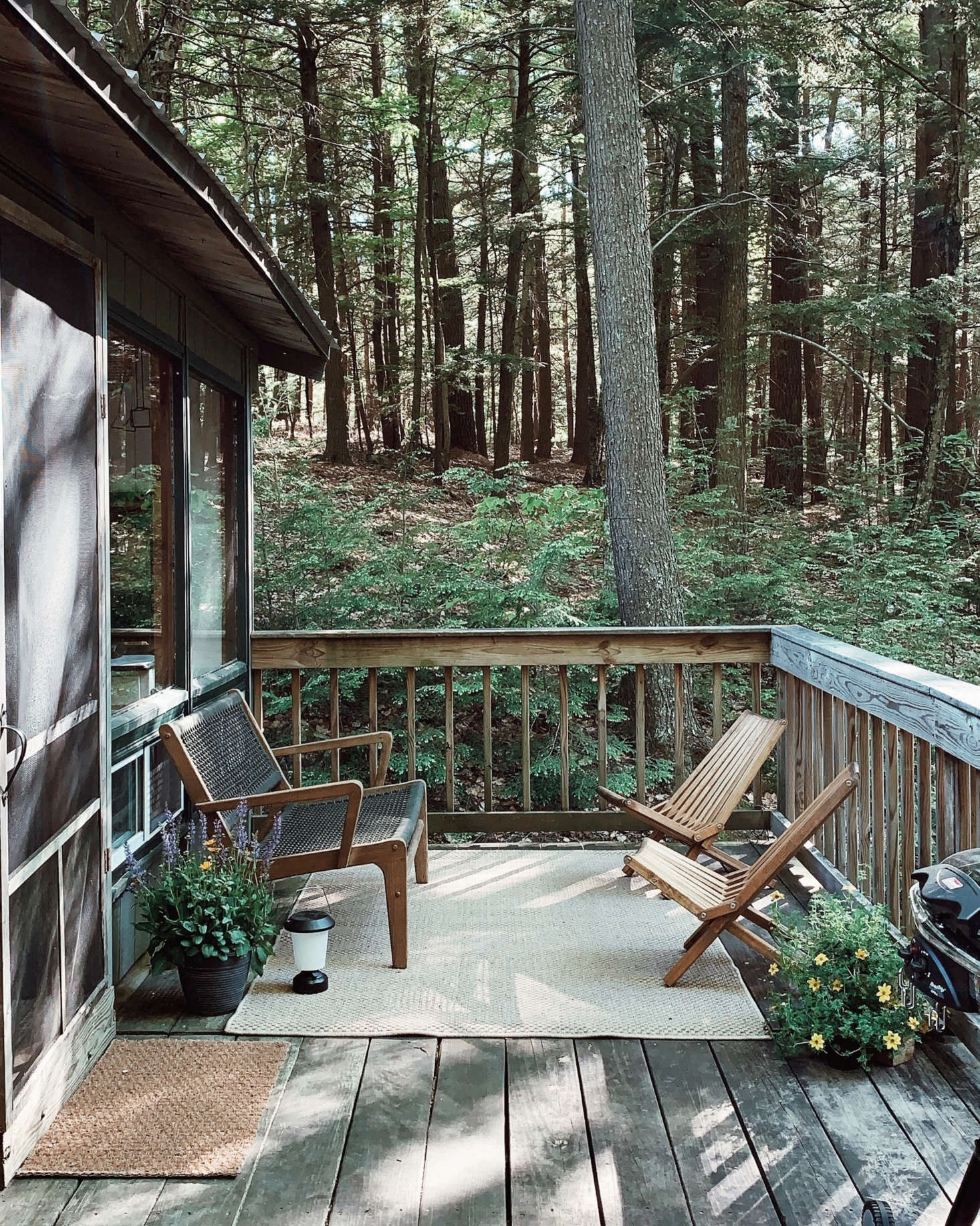 """The deck is a quiet place for reading or relaxing. It also serves as a spot for outdoor showers, of sorts: """"When we need to take a 'shower,' we put one of our eight-gallon water jugs on the edge of our deck, right above a built-out shower platform, then open the spigot and run down to stand underneath!"""" Saunders says."""