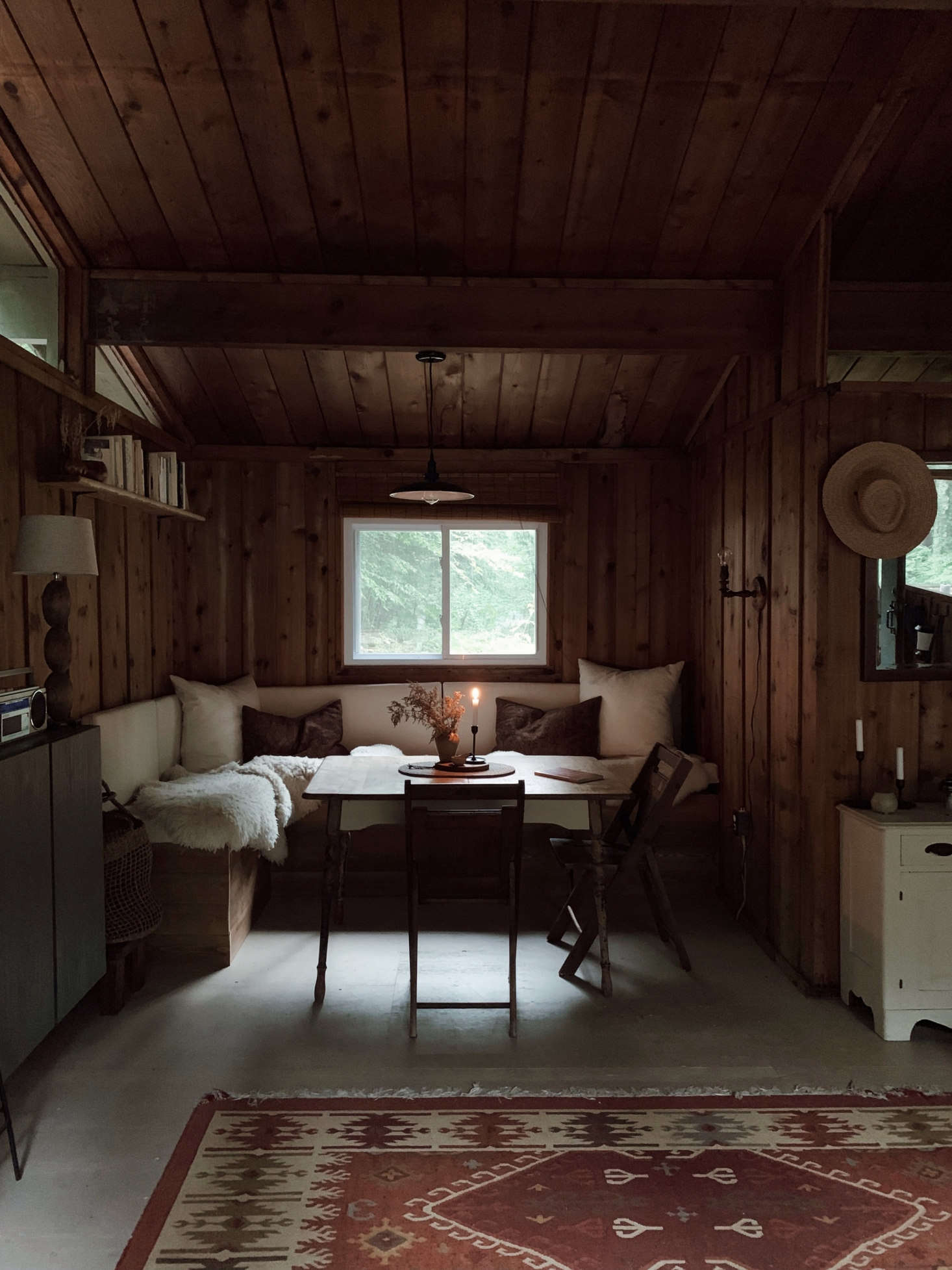 """The dining nook is the couple's proudest DIY. """"We designed it ourselves after watching a number of different YouTube tutorials,"""" Saunders says. """"The frame is 2x4s and plywood, and I made the removable cushions out of plywood, upholstery foam, and canvas. I covered it in sheepskins to make it extra cozy for us and also for our dog, who loves to nap there."""""""