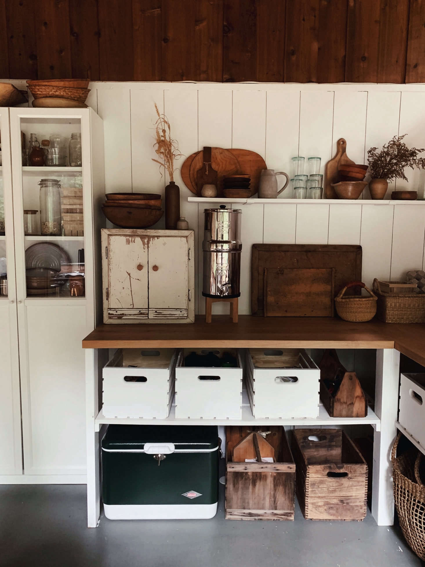 """""""Almost all of the glasses, cutting boards, and cutlery came from the dump swap shop,"""" Saunders says. Note the metalBerkey water filter propped up on a retrofitted drink stand. The tongue-and-groove walls are painted in Behr Ultra Pure White."""