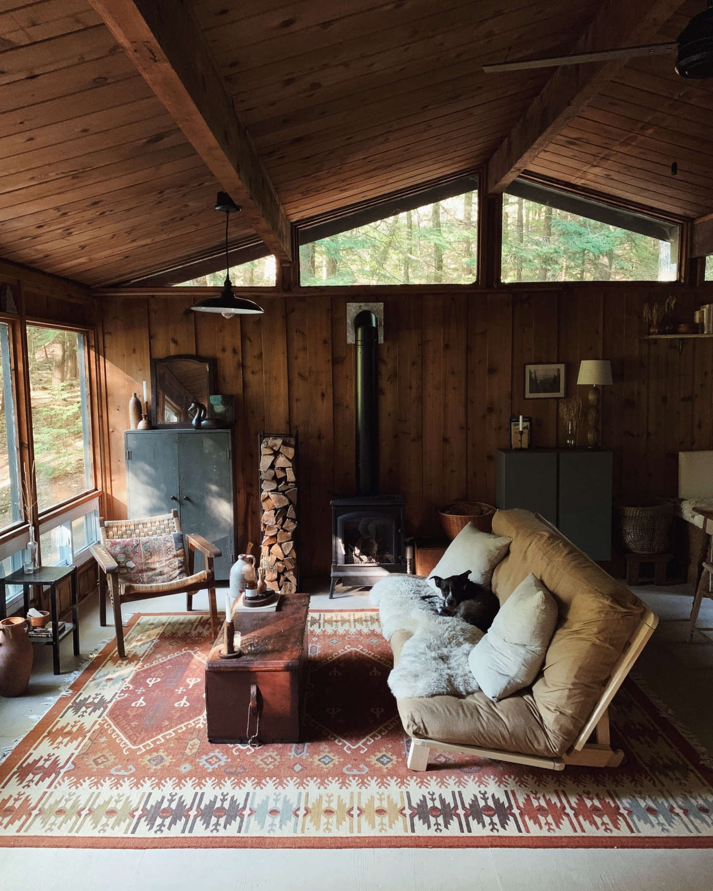 """The cabin's living room, with a futon by KD Frames. The cabinet on the back wall, by the window, is the one that inspired much of the interiors. The rug was part of the package: """"It's important to me to keep a little piece of the previous family in the cabin,"""" Saunders says."""