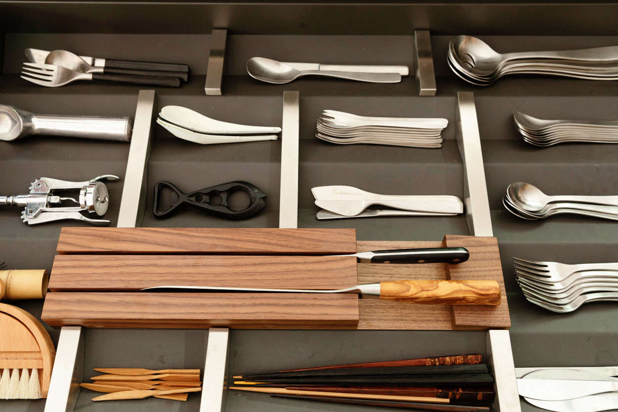 "Bulthaup's B3 drawer inserts of aluminum, steel, and wood can be arranged and rearranged. The family's everyday flatware is Muji's 18-8 Stainless Steel Cutlery designed by Jasper Morrison (which starts at $2 for a small fork); in the back, Yanai keeps ""examples of other cutlery I like by Jasper Morrison for Alessi and also Sori Yanagi."""