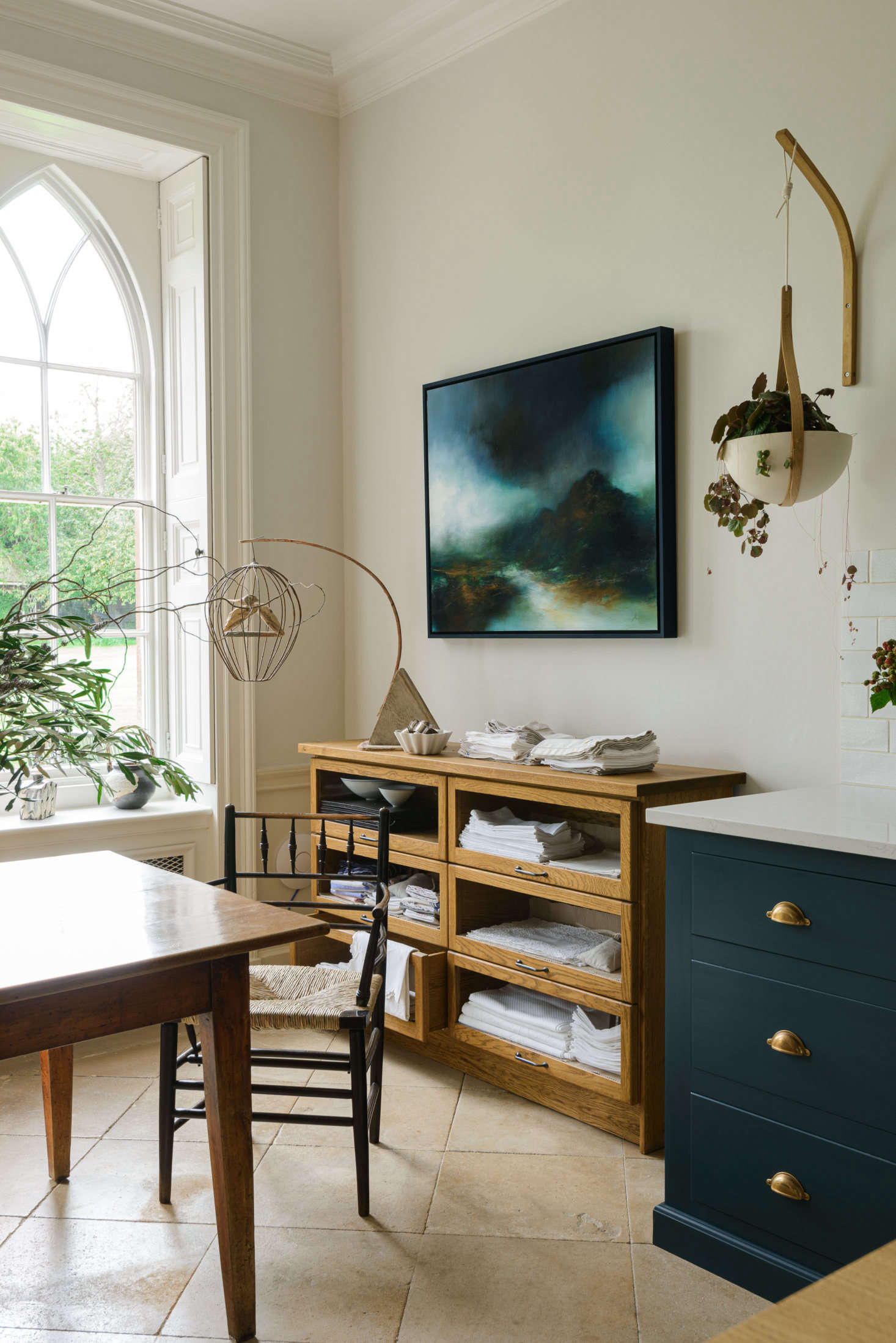 The glass sideboard, for storing kitchen linens, is from deVOL&#8