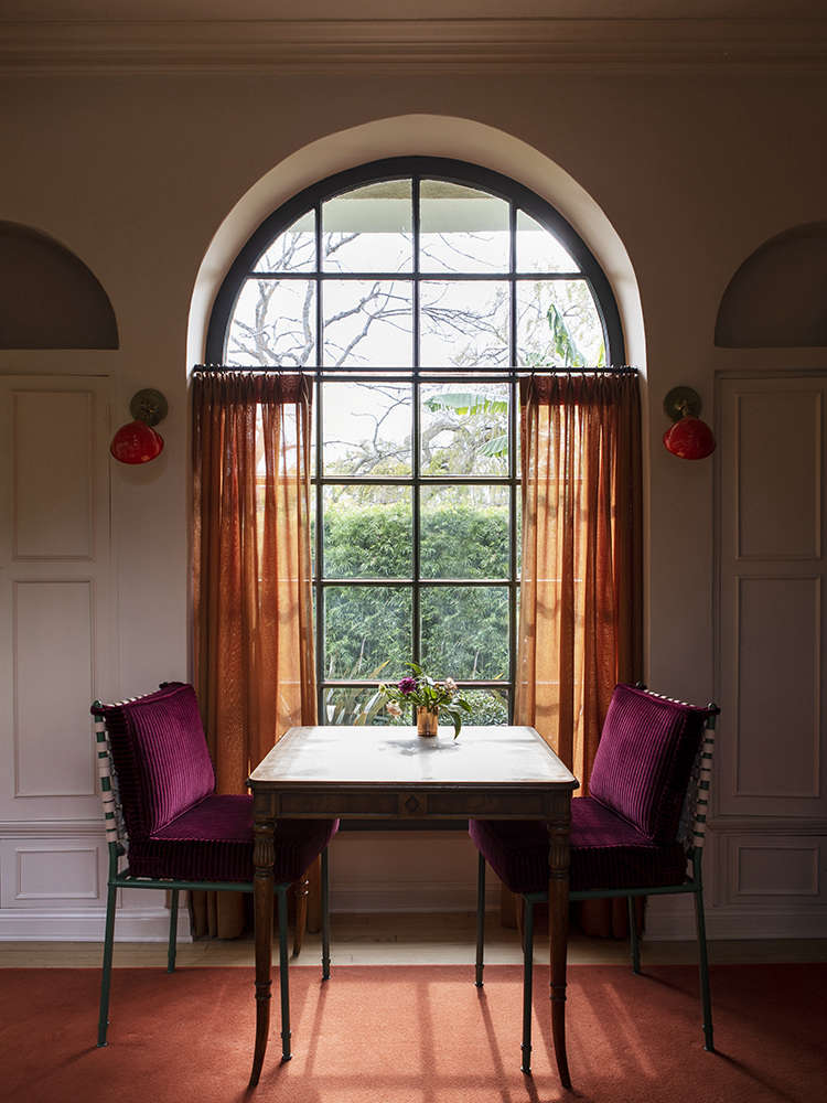 A favorite color moment: curtains in a linen from Bart Halpern against Casa Midy Altavista chairs cushioned in crimson corduroy from Pindler & Pindler. The antique table is used for playing chess and backgammon. The red sconces, from the family&#8