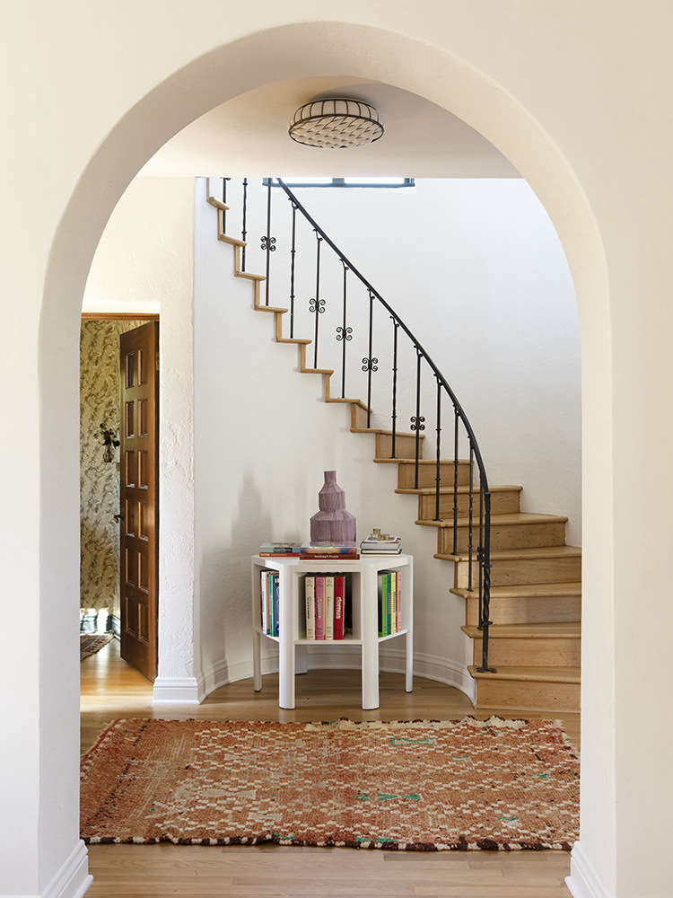 A Martin & Brocket Library Table stands in the entry under a curved stair. &#8