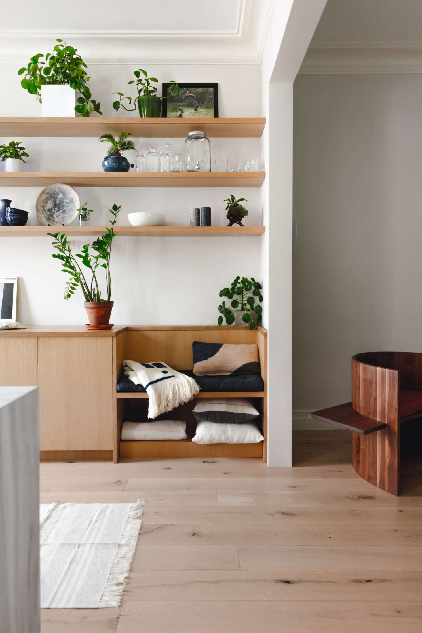 The architects inserted a little bench next to the cabinets (cushioned with pillows and throws from Minna). Of the couple&#8