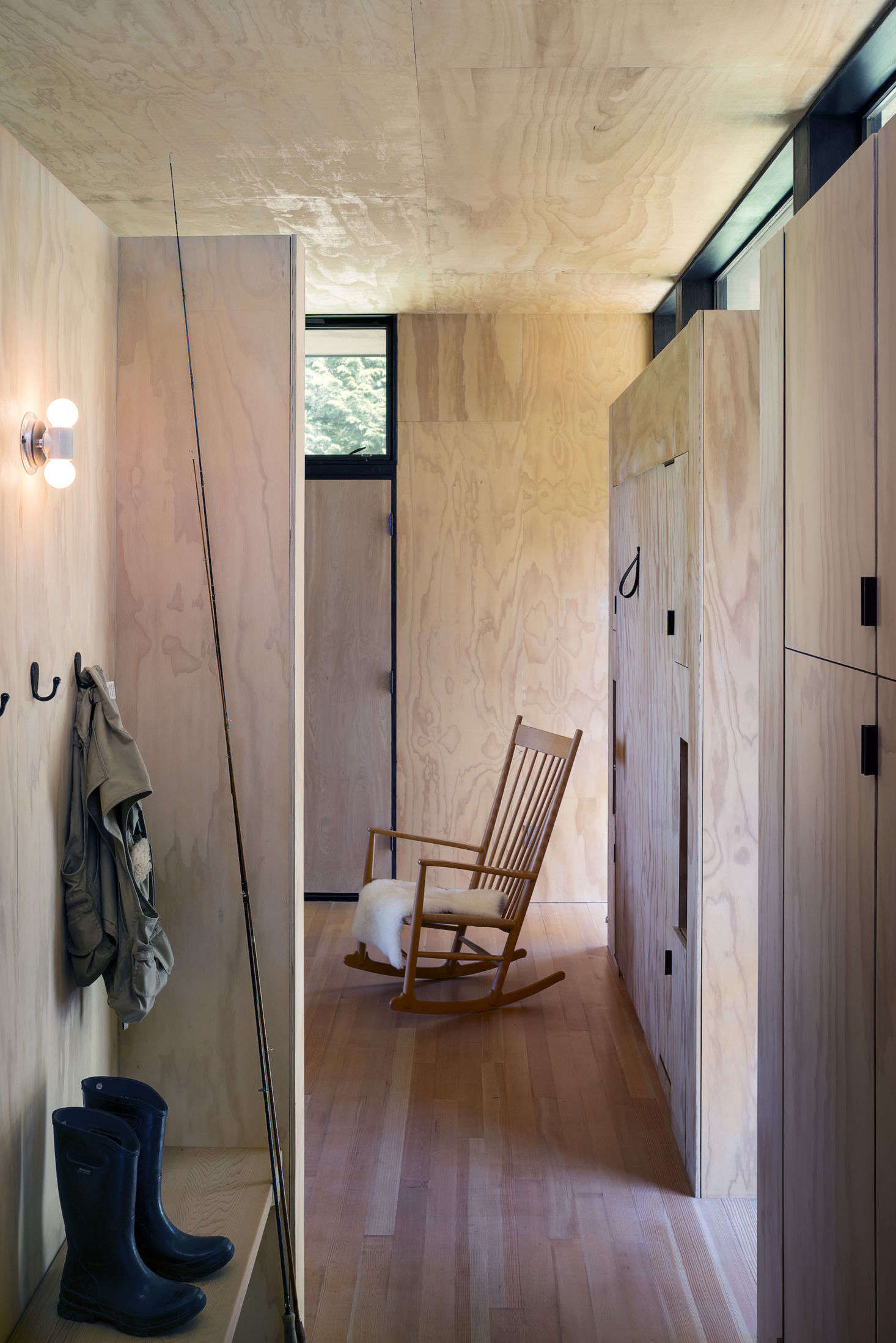 The entry into the main cabin. Just beyond is a Hans Wegner rocking chair and a hidden Murphy bed on the right wall of the living room. The flooring is fir hardwood, and the ceiling and walls are clad in pine plywood.