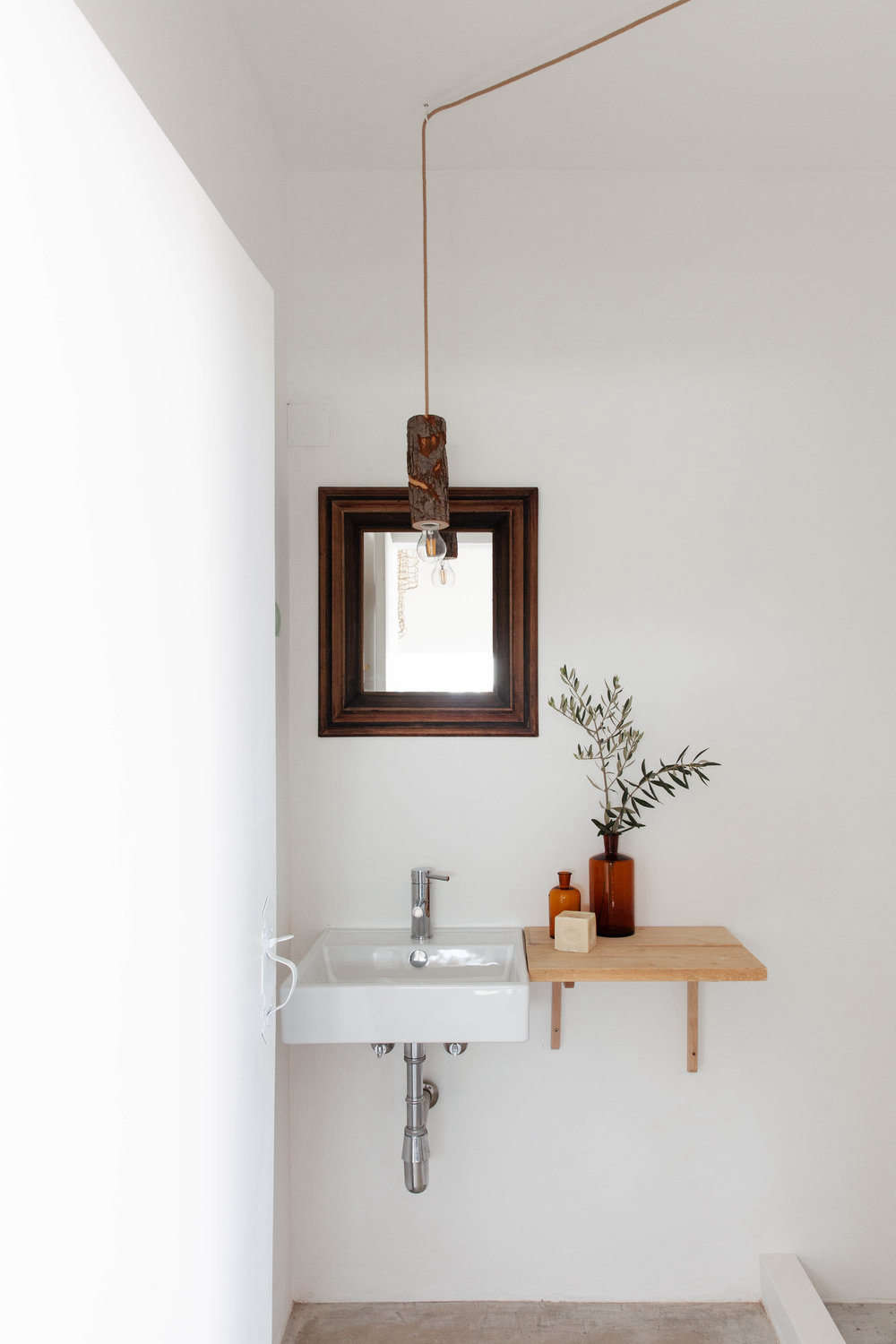A wood ledge extends sink-side space in one of the baths. Note the rustic pendant light, too.