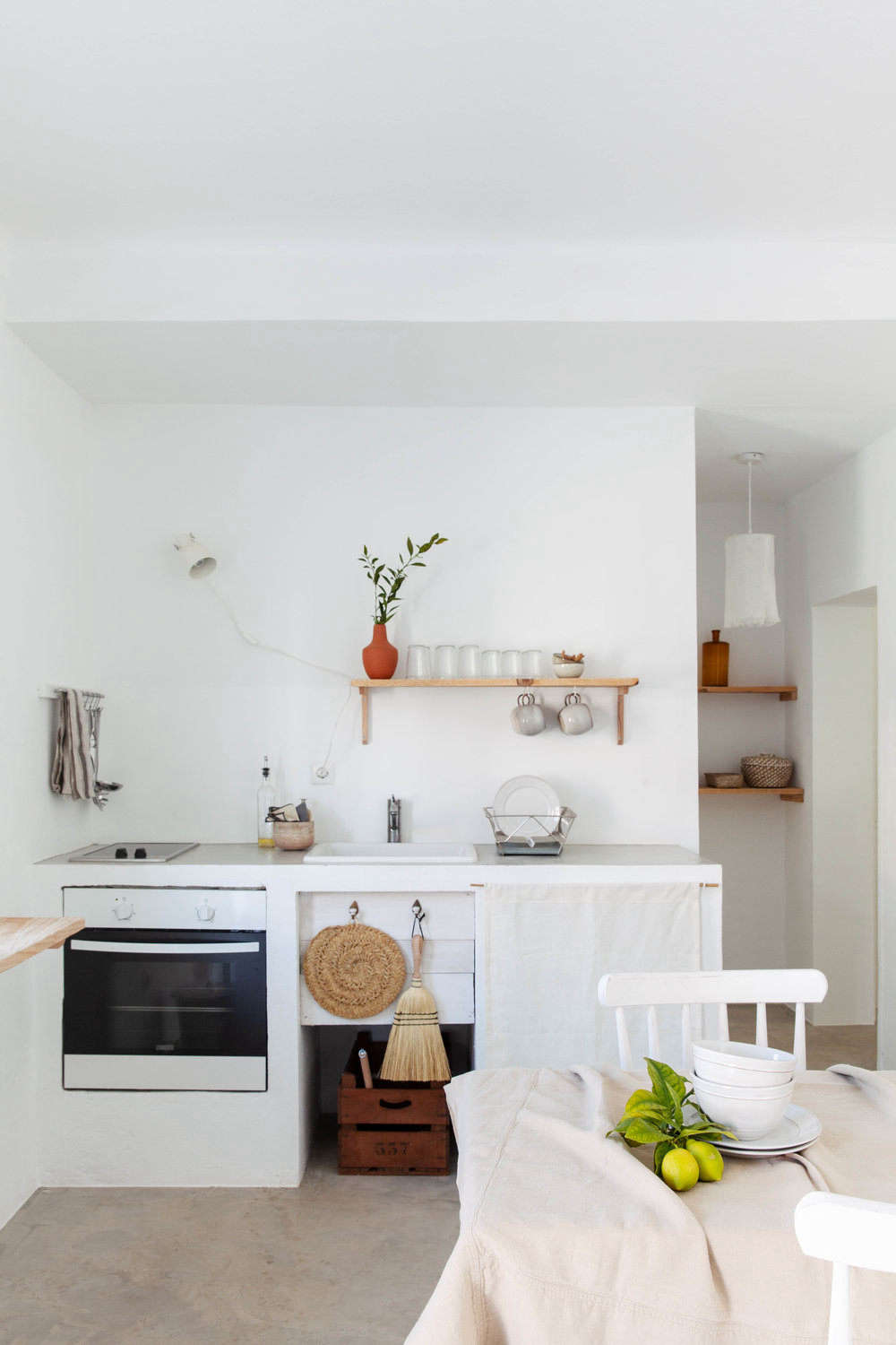 In another simple kitchen, a cabinet is fitted with linen skirt. Also on hand: a hand broom and woven trivet.
