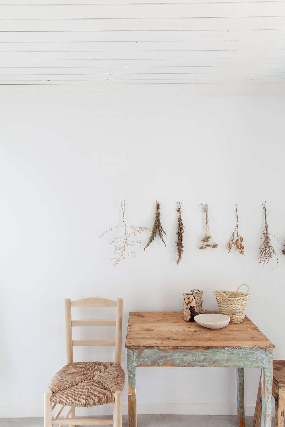 Bundles of dried flowers and stems make for a sweet vignette above a dining table.