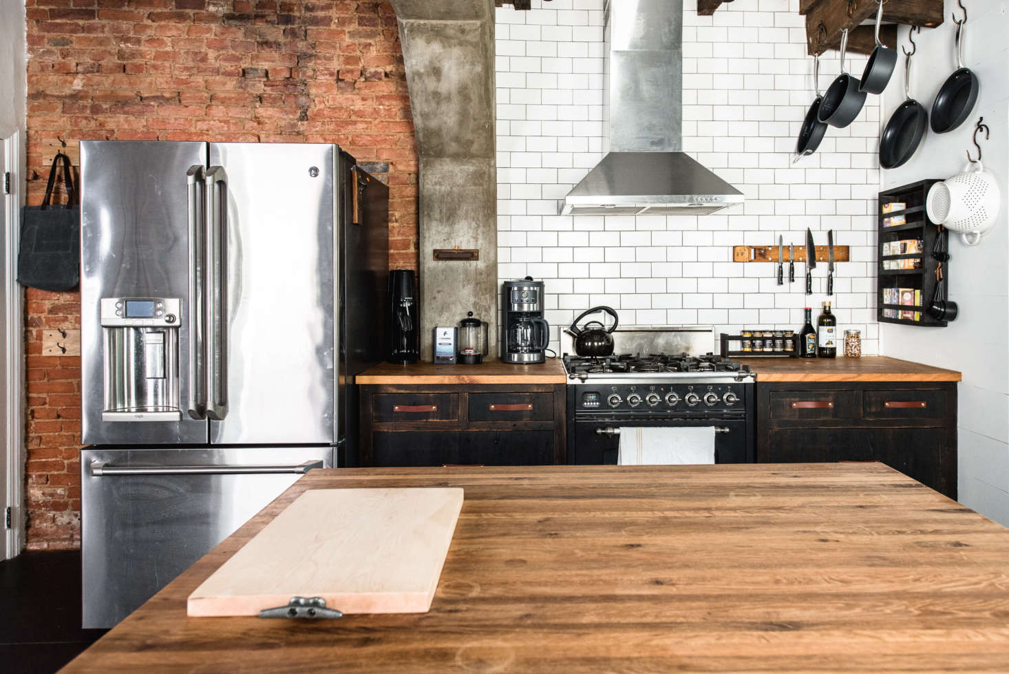 As a counterpoint to the patinated surfaces, they installed industrial-style appliances, including a GE fridge and Ilve gas range. The 3-by-6-inch subway tile is Daltile from a local supplier, but they point out, is also available at Home Depot. &#8