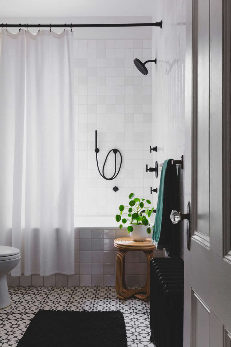 Like the entry, the bathroom has a black-and-white floor of Agadir Cement Tile: &#8