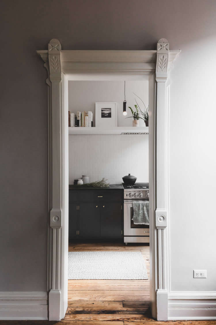The couple added a kitchen to the parlor floor, framed here by moldings painted Benjamin Moore&#8