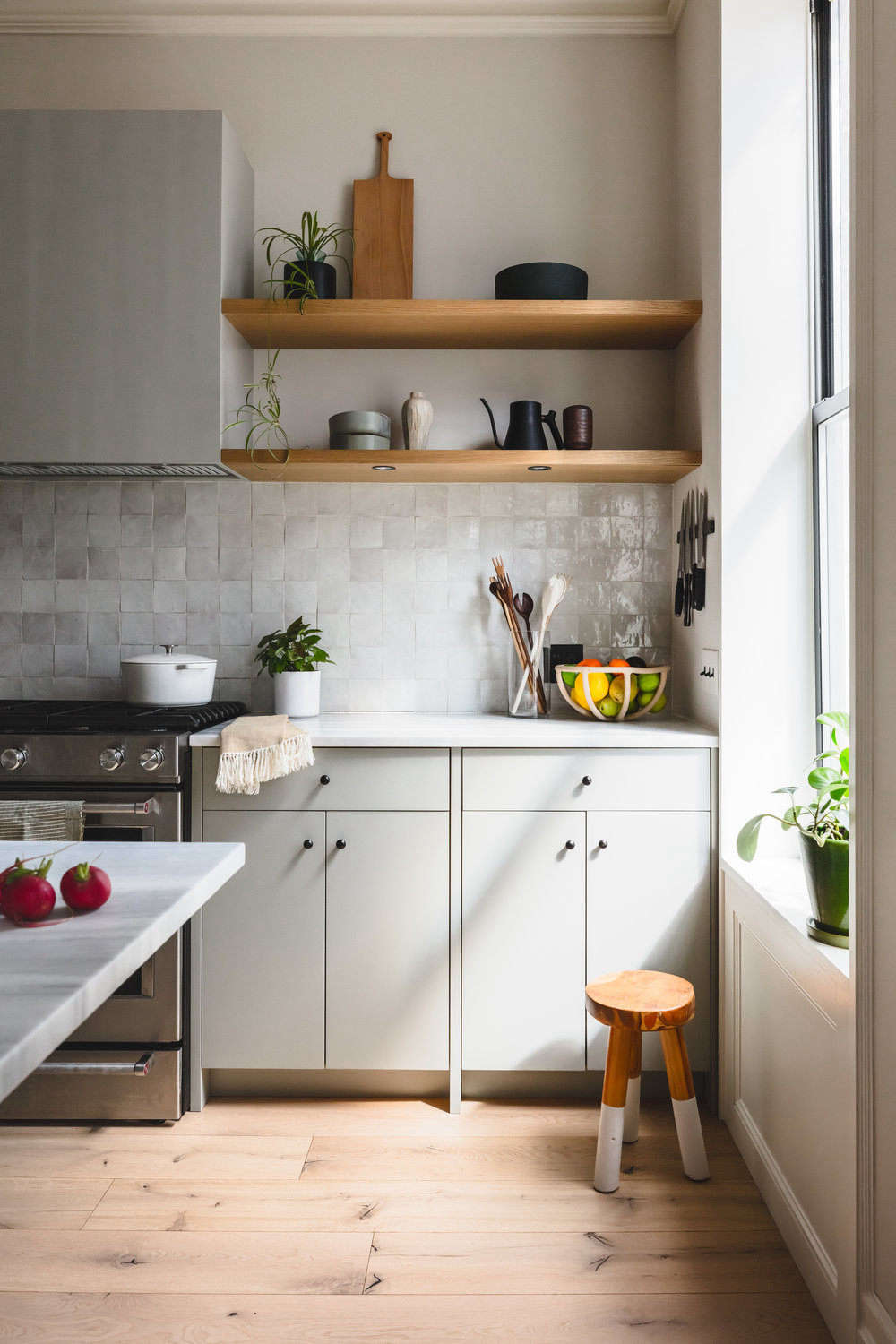 The counter and open shelves are reserved for a few kitchen tools, such ascutting boardsand wooden spoons by Allison Samuels of Two Trees Studio and aTerracotta Fruit Bowlby Virginia Sins. Dishes and the couples&#8