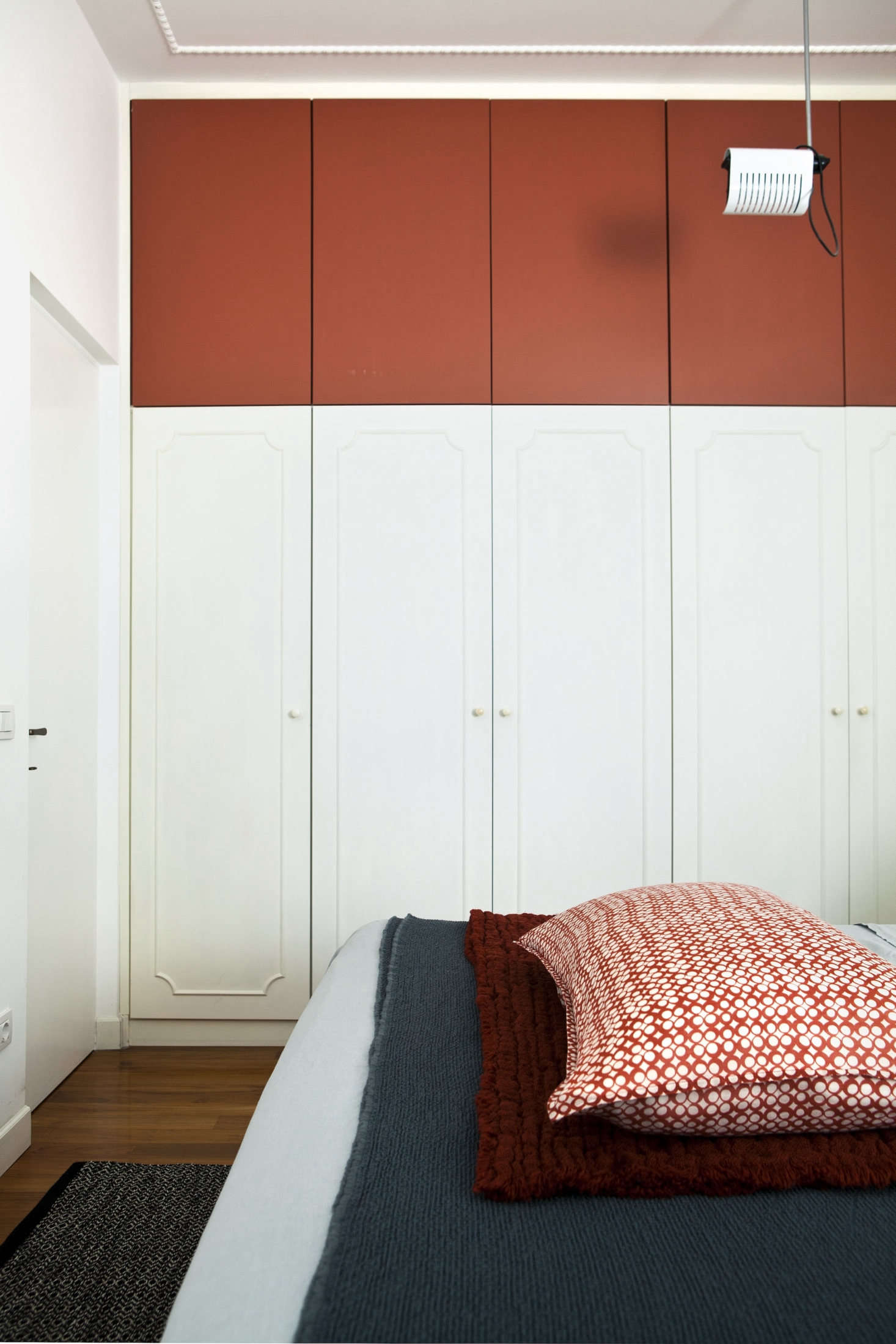 In the bedroom, the architects integrated existing built-in wardrobes with an added row of storage on top, painted also, strikingly, in Tuscan Red.