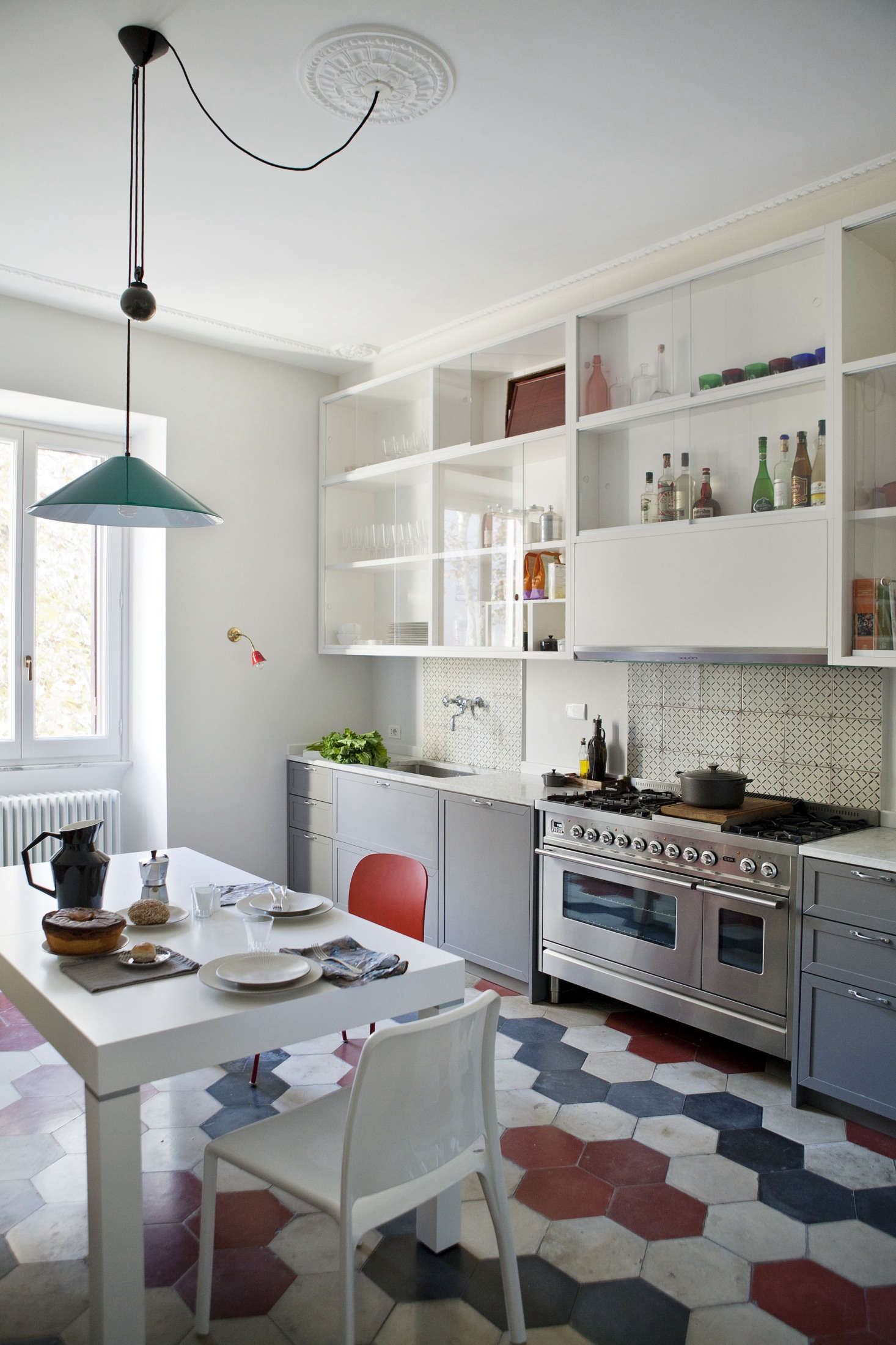 In the kitchen, a reclaimed cement-tile floor sets the stage for a motif of dusty reds and blues that appears throughout the house. &#8