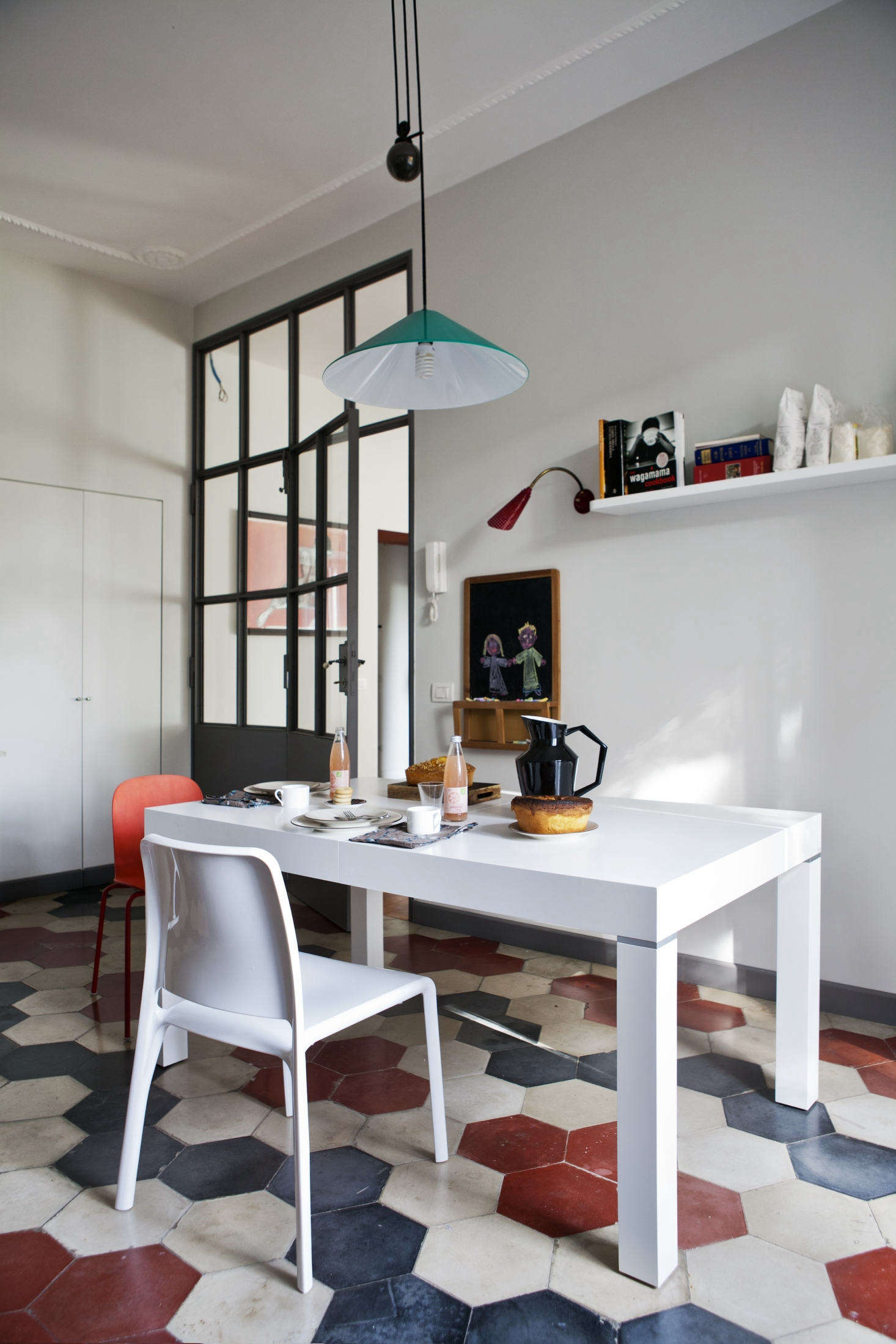 A bright turquoise pendant—theAggregato by Artemide—hangs above the breakfast table.