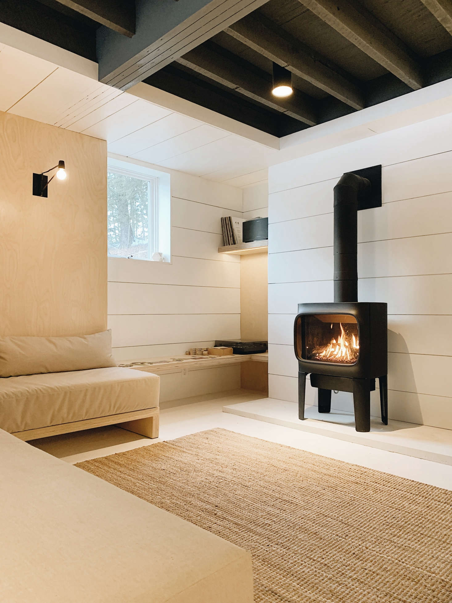 The two sofas can be pushed together to form a double bed. The existing fireplace was replaced with a gas stove, the Jøtul GF 305 (controllable via the Nest thermostat), and the walls are clad in shiplap paneling painted Valspar&#8