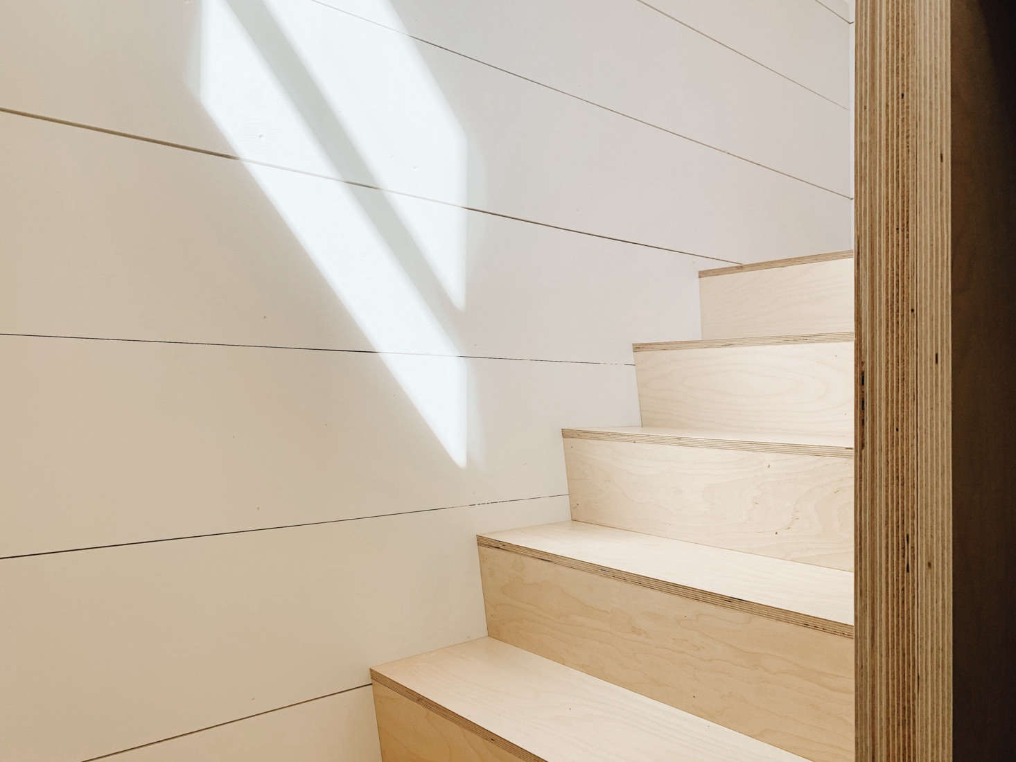 Shiplap paneling and birch plywood stairs. Note the door frame&#8