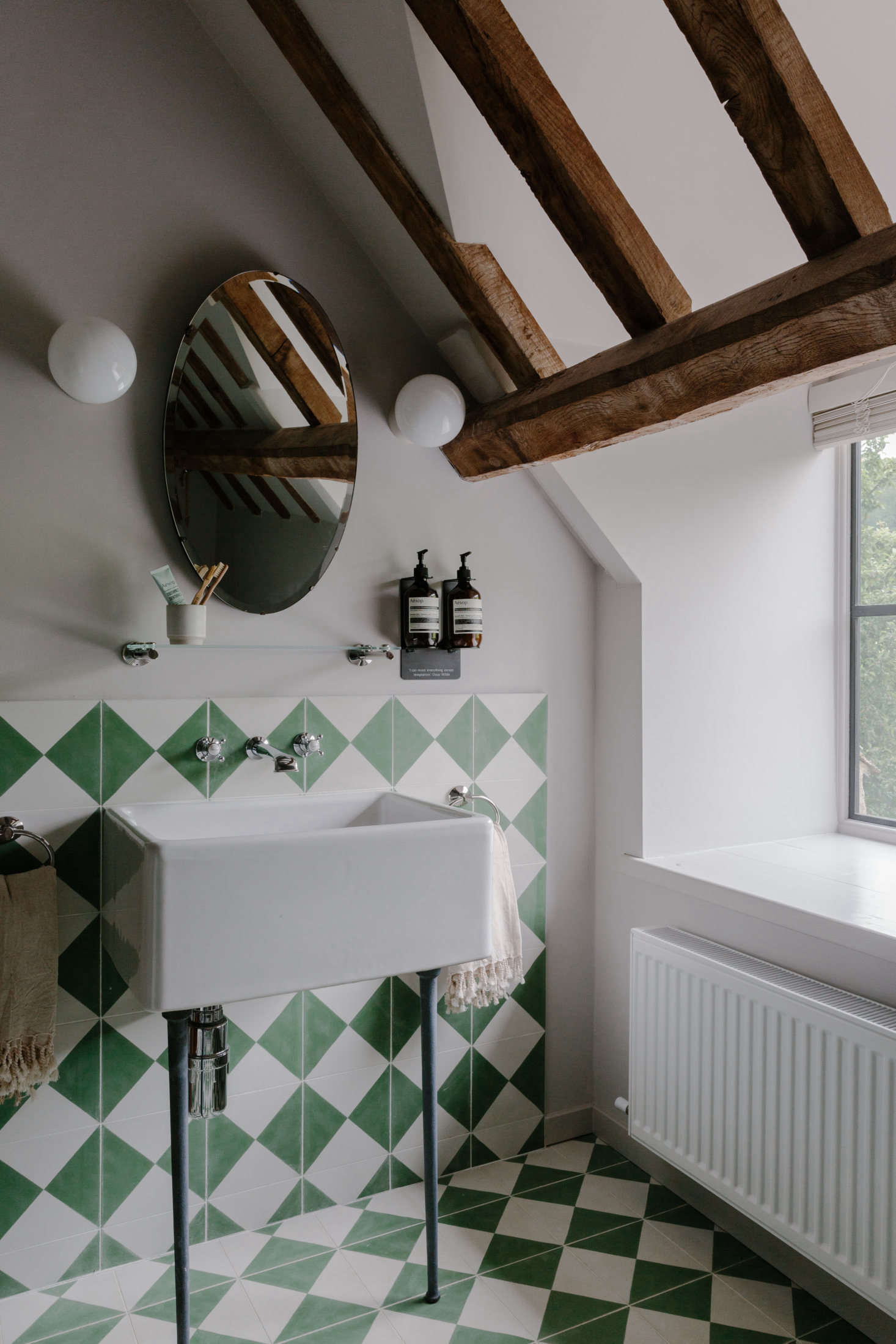 The bathrooms are tiled in green and white patterns, all sourced from Bert and May.