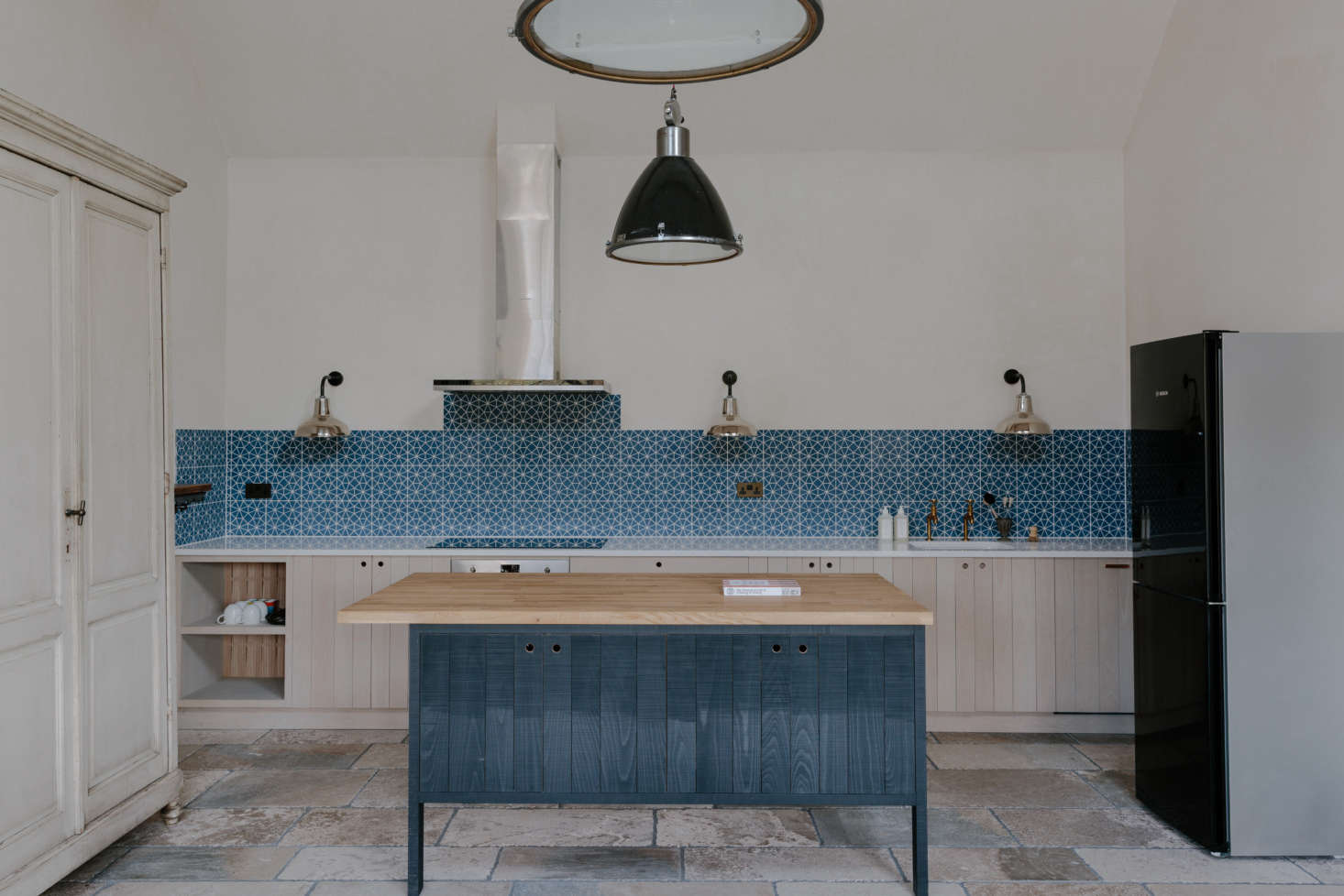 The cottage kitchen—including the double faucet—is by DeVol, with a backsplash of blue Bert and May tiles and industrial lights from Trainspotters.