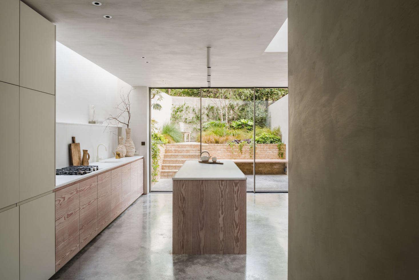 O nível do porão apresenta piso de concreto polido por toda parte e se estende até o jardim, logo após as portas de correr da cozinha.