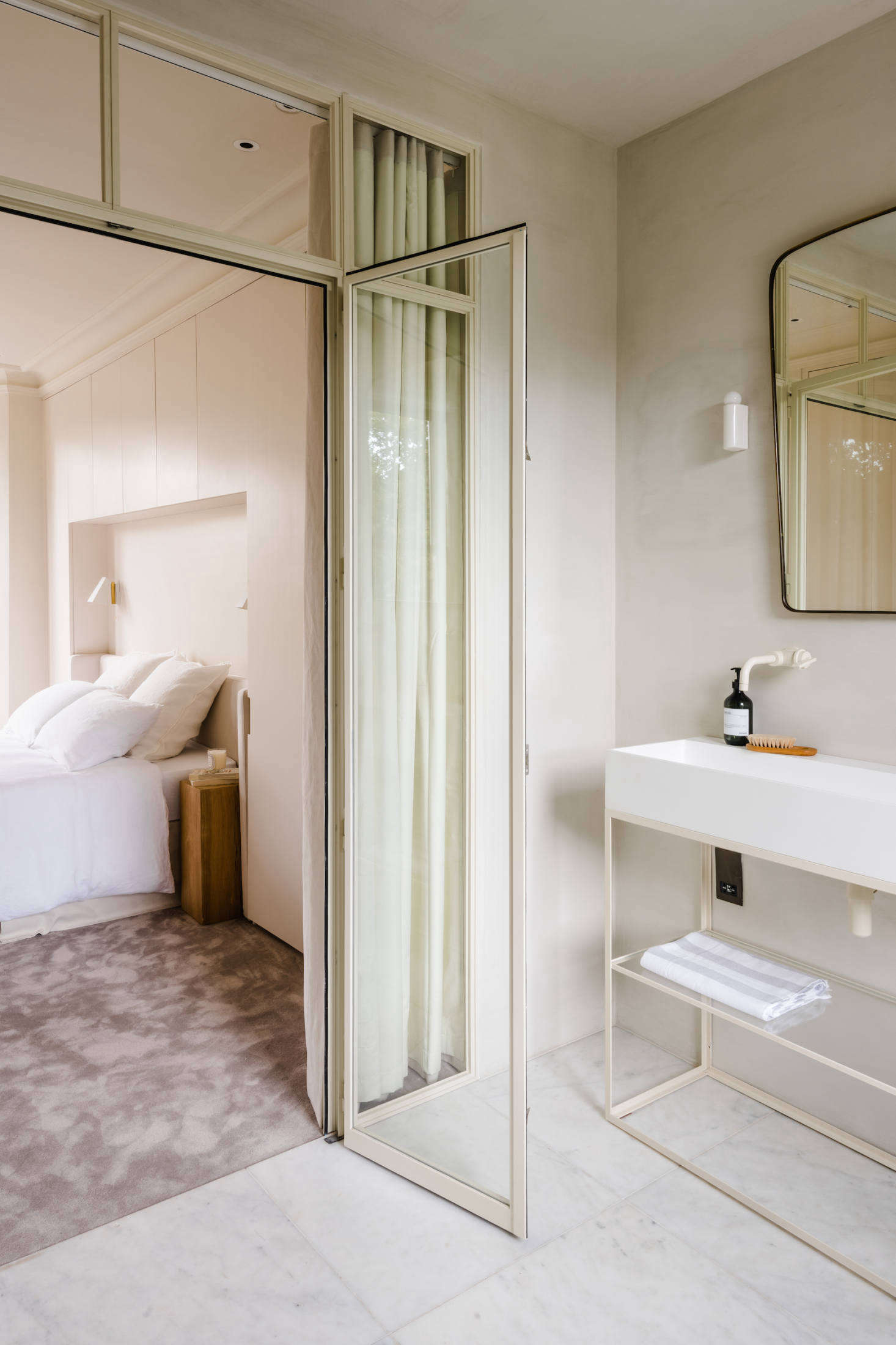 A Crittall steel and glass door separates the bedroom from the ensuite bath. &#8