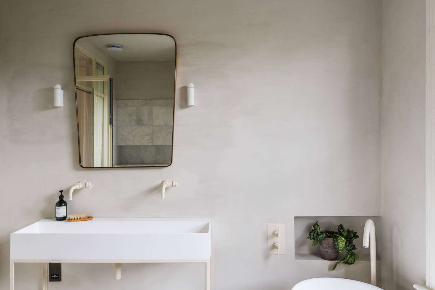 All the fixtures, powder-coated oyster white, are by Studio Ore. The 50s Italian brass mirror is from Béton Brut.